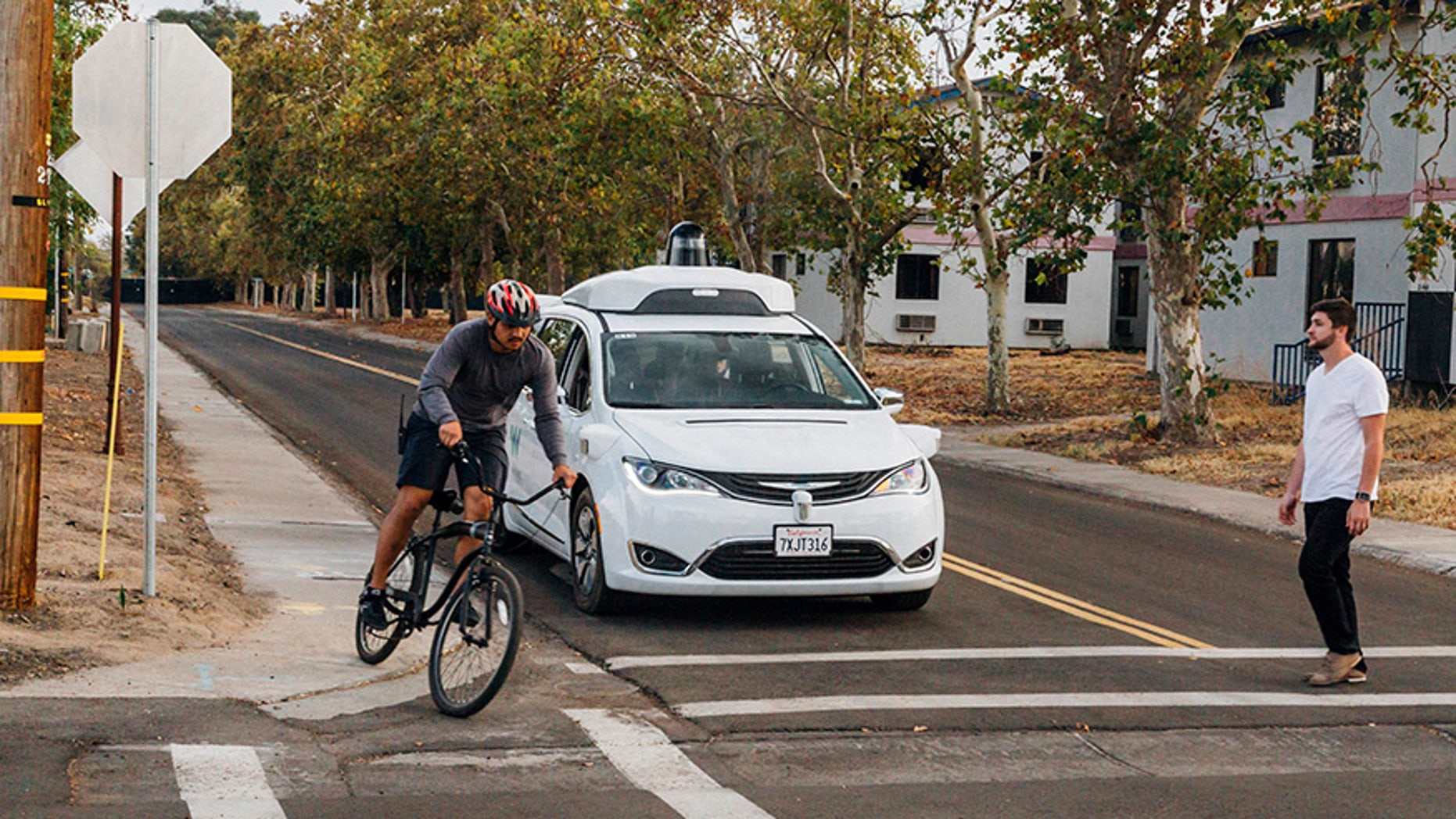 This Sunday, Oct. 29, 2017, photo provided by Waymo shows a Chrysler Pacifica minivan equipped with Waymo's self-driving car technology, being tested with the company's employees as a biker and a pedestrian at Waymo's facility in Atwater, Calif. Waymo, hatched from a Google project started eight years ago, showed off its progress Monday during a rare peek at a closely guarded testing facility located 120 miles southeast of San Francisco where its robots complete their equivalent to driver's education. (Julia Wang/Waymo via AP)