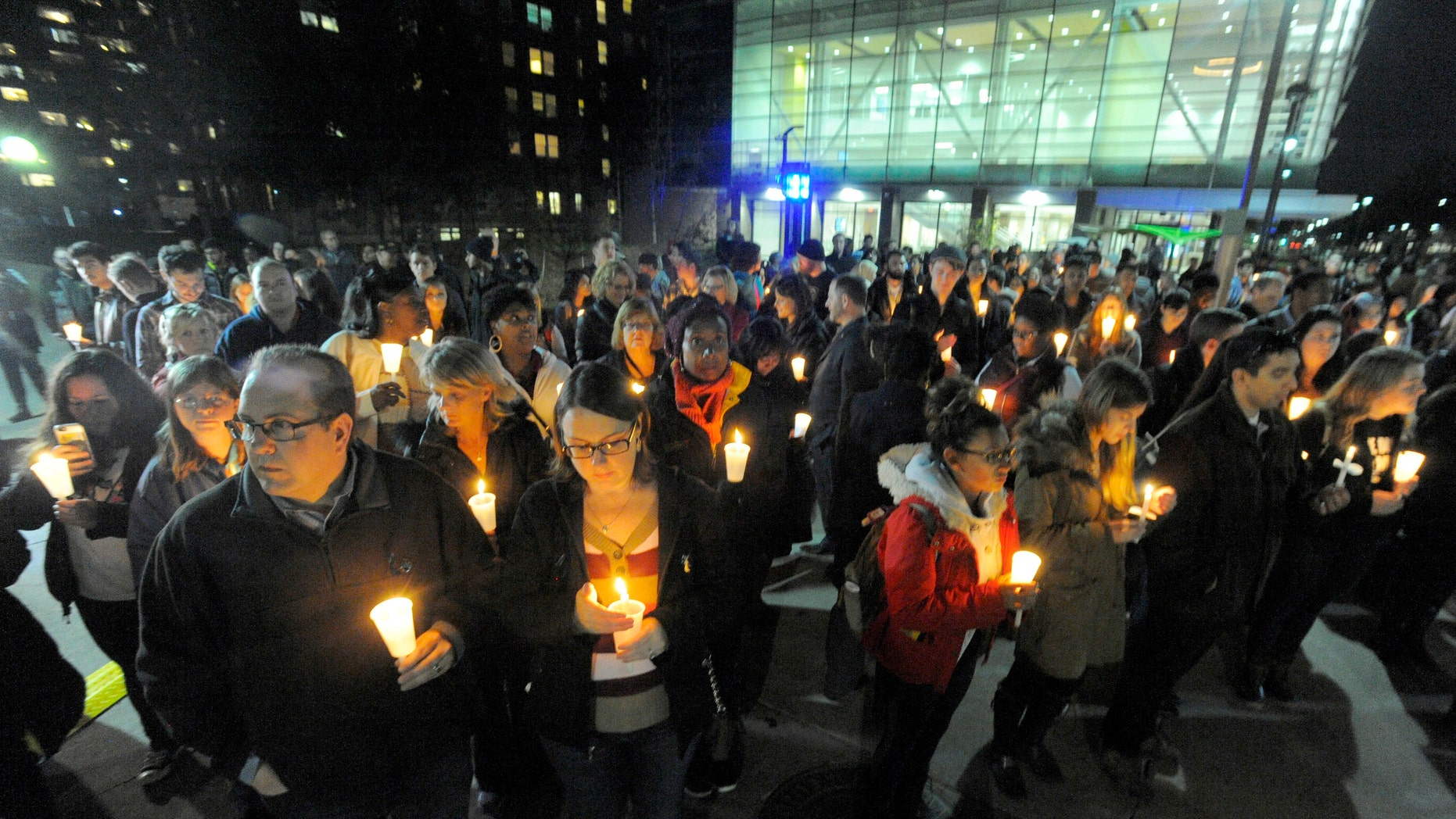A large group gathers during a candlelight vigil on the campus of Wayne State University for Wayne State University campus police officer Collin Rose, Tuesday, Nov. 29, 2016, in Detroit. Rose was shot as he tried to arrest DeAngelo Davis, who was arraigned Friday on murder and gun charges. Rose died last Wednesday at a hospital. (Steve Perez/Detroit News via AP)