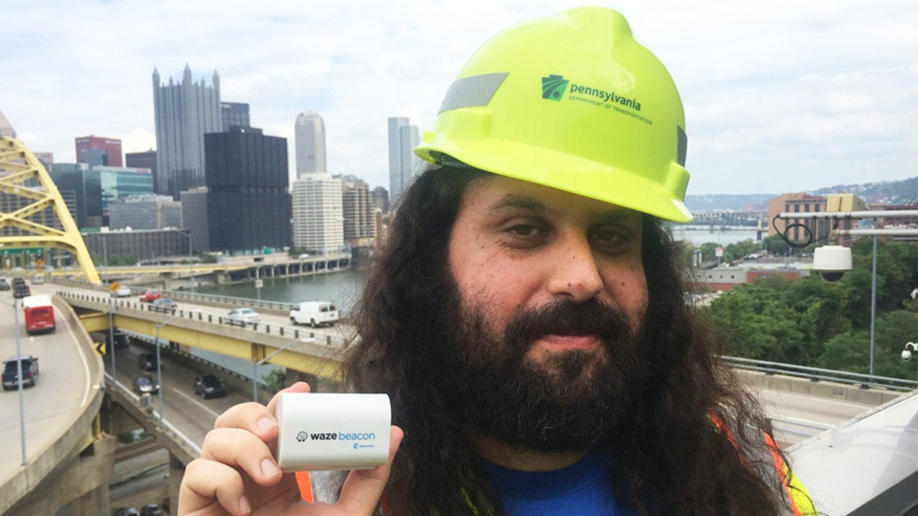 Waze system operation engineer Gil Disatnik holds a Waze beacon in Pittsburgh.
