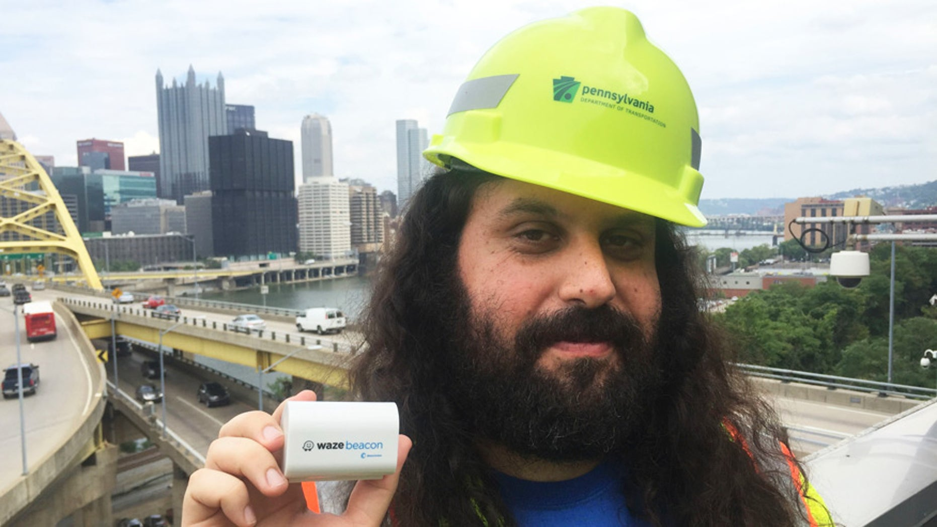 Waze system operation engineer Gil Disatnik holds a Waze beacon in Pittsburgh.
