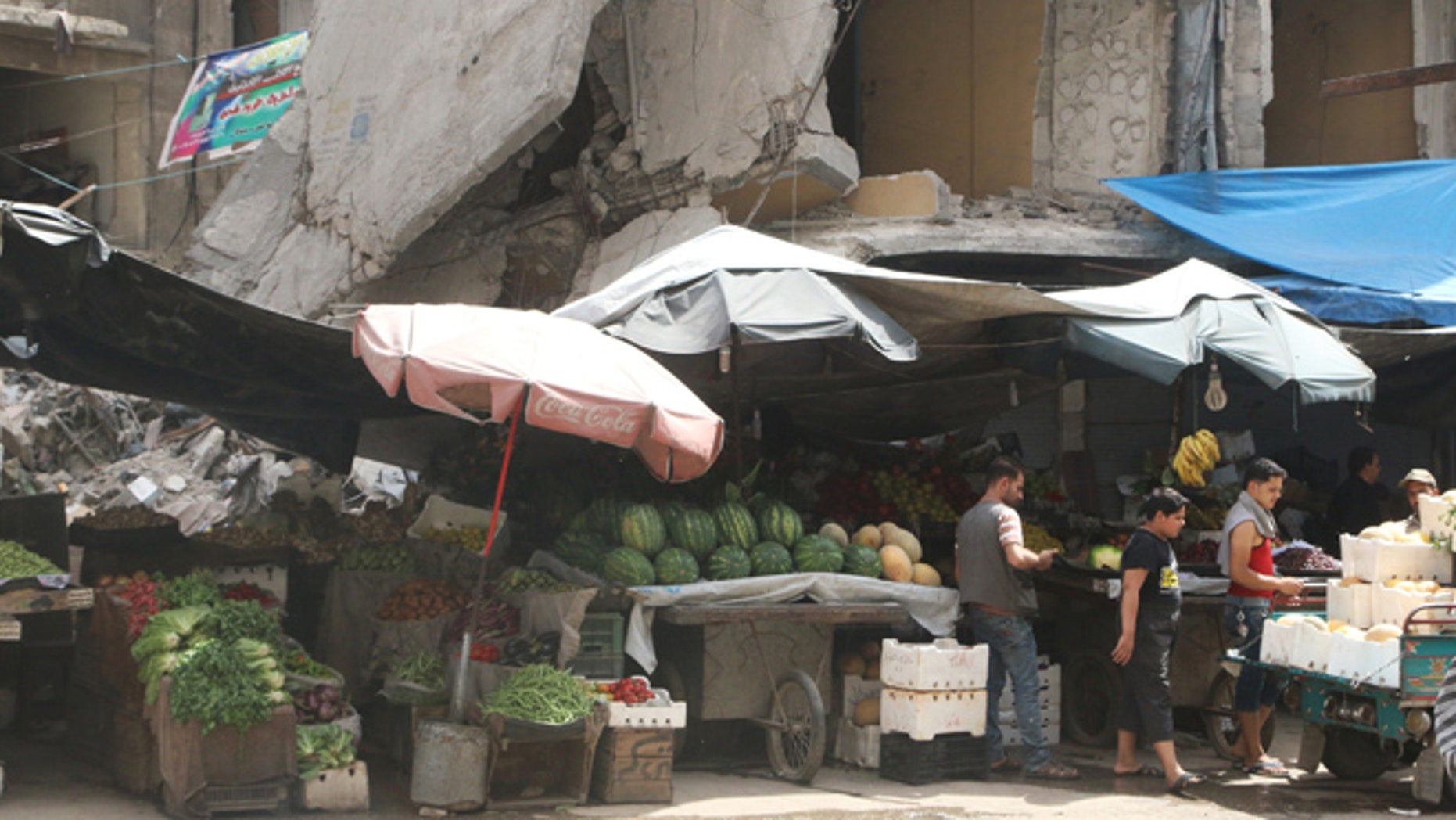 Vendors wait for customers near their stalls erected in front of damaged buildings during the holy month of Ramadan in the rebel held area of Aleppo's al-Shaar district, Syria, June 15, 2016. REUTERS/Abdalrhman Ismail - RTX2GDRZ