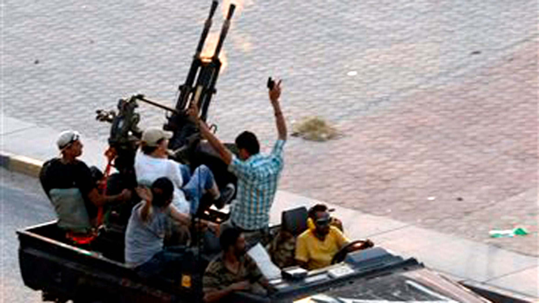 Libyan rebels fire into the air in the Bab El Bahrah district in Tripoli, Tuesday, Aug. 23, 2011. Hundreds of Libyan rebels blasted through the green gates of Moammar Gadhafi's Bab al-Aziziya compound in Tripoli Tuesday after five hours of intense fighting around it.