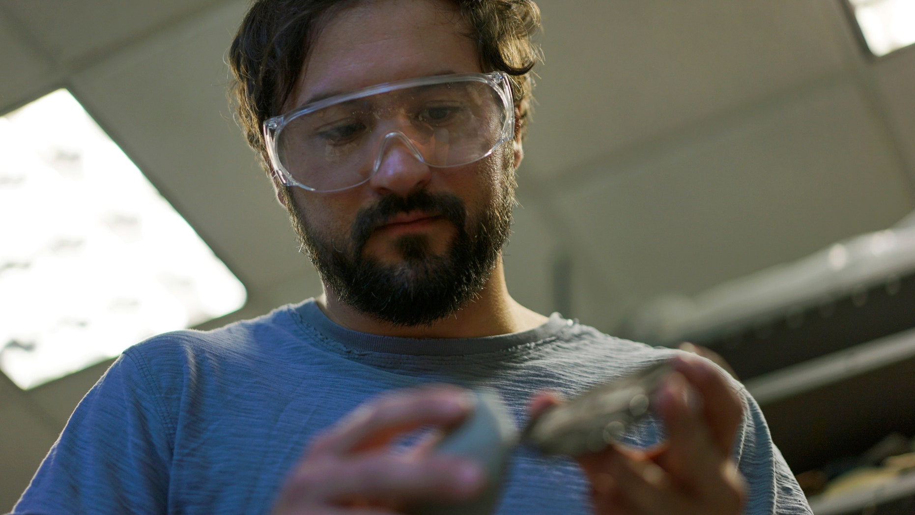 In this June 1, 2017, photo, Metin Eren, an archaeologist at Kent State University, looks at a newly chipped flake of obsidian in Kent, Ohio. Eren runs a newly-opened laboratory which makes replicas of ancient arrows, knives, and pottery to be shot, crushed, and smashed. It's allowing researchers to learn about engineering techniques of the first native Americans without destroying priceless genuine relics in the process. (AP Photo/Dake Kang)