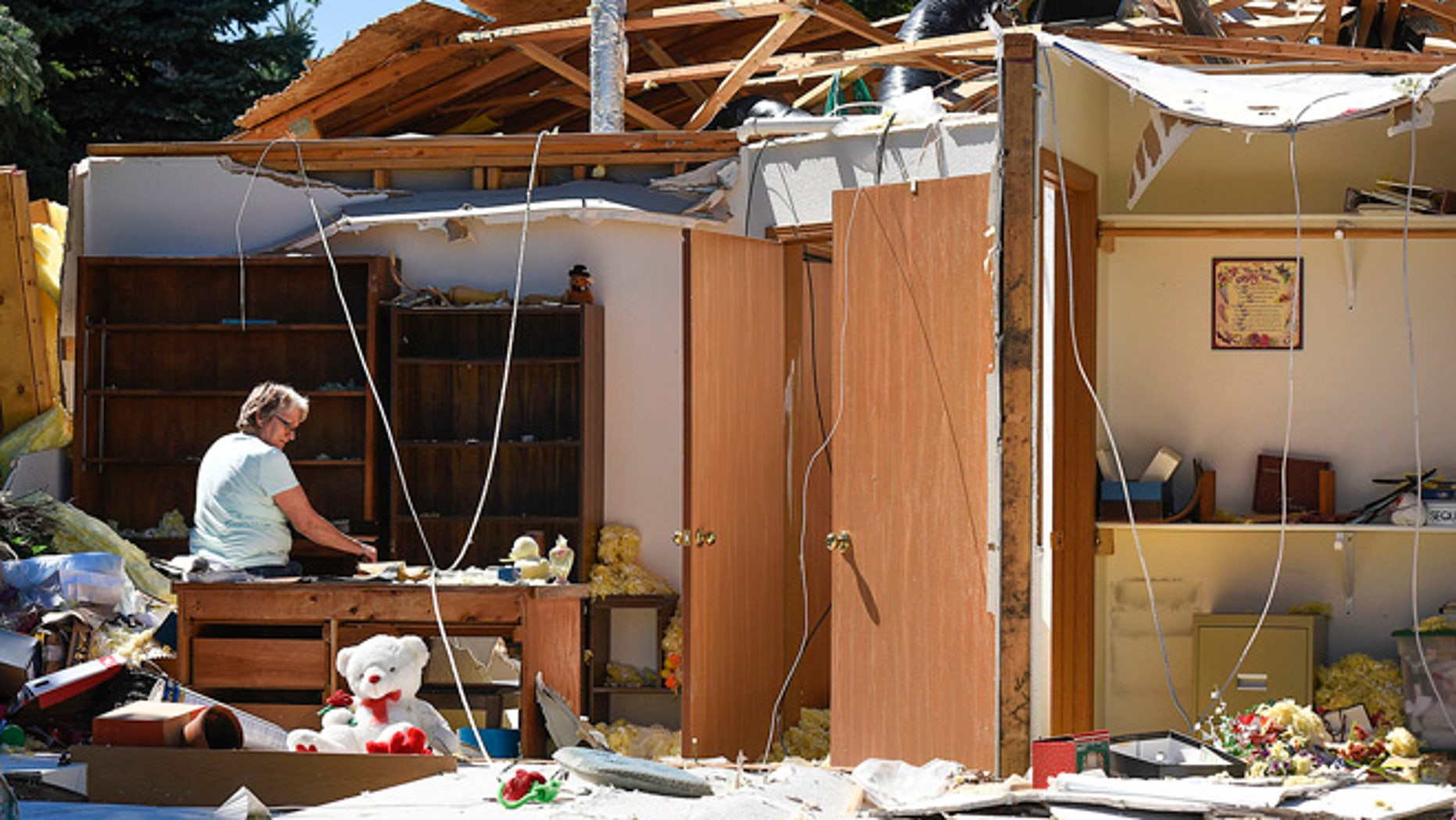 Marilyn Kuechle takes a break while packing the belongings in what's left of her sisters home Tuesday, July 12, 2016, after a tornado destroyed the home Monday night in Watkins. (Jason Wachter/St. Cloud Times via AP)