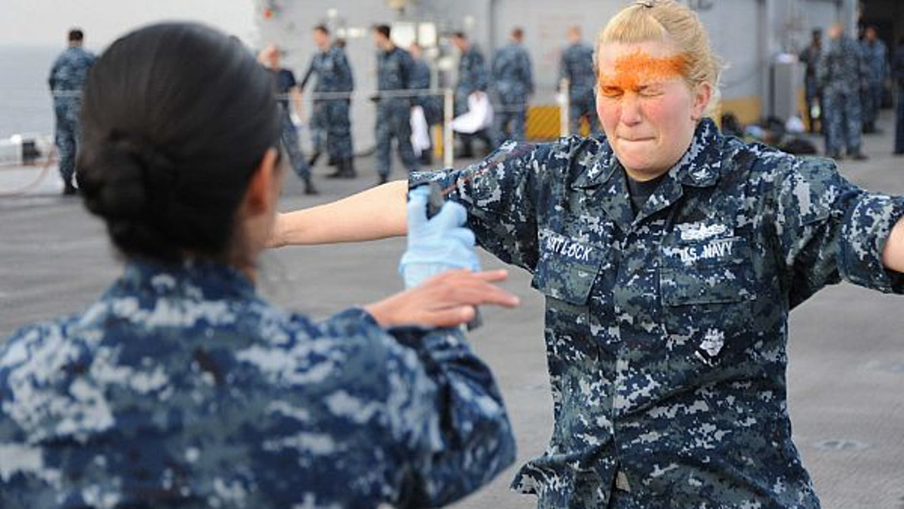 Master-at-Arms 1st Class Cathy Garcia sprays pepper spray into the eyes of Electronics Technician 3rd Marie Matlock.