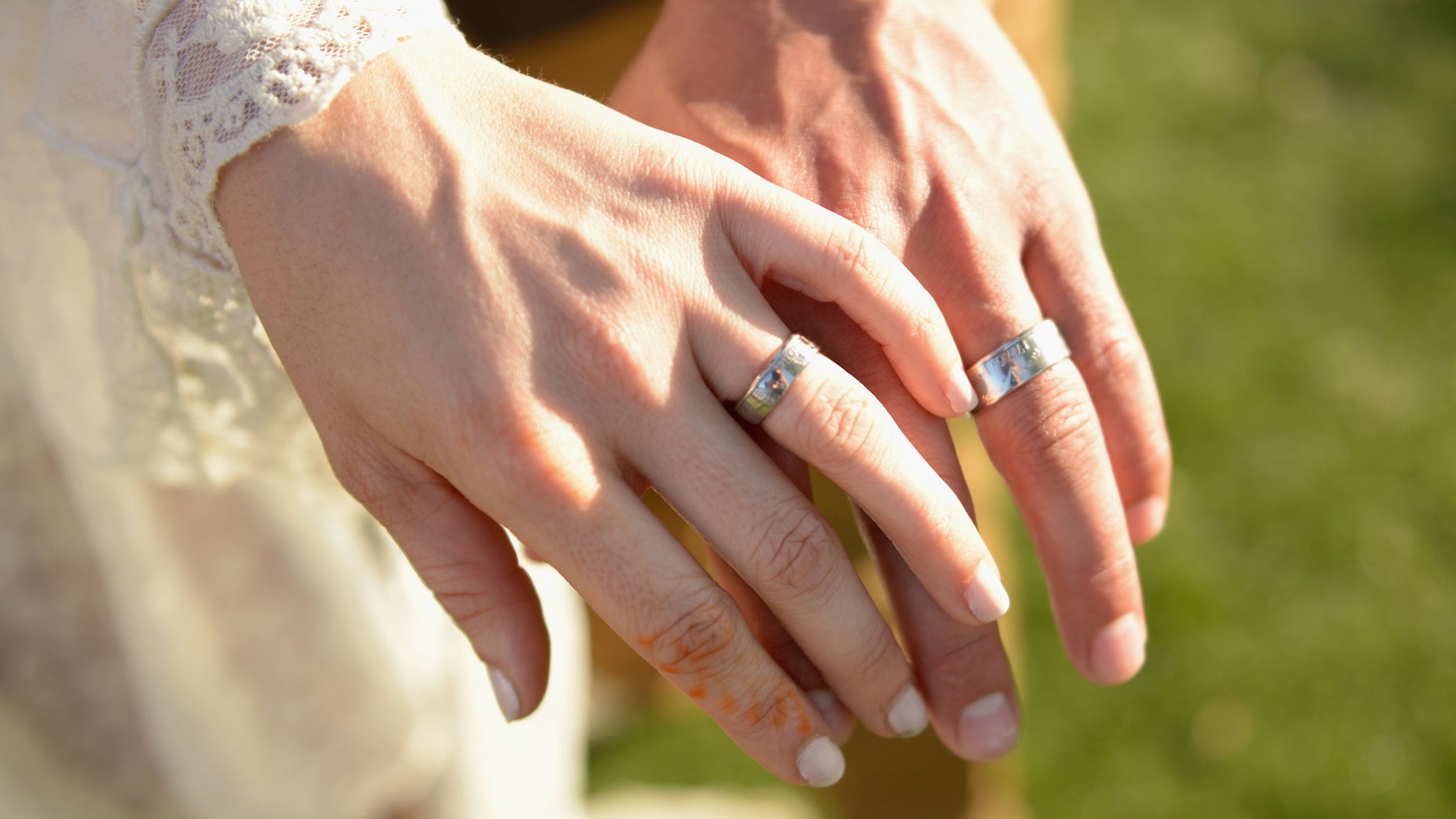 The hands of bride and groom are seen in Indio, California, April 11, 2015.