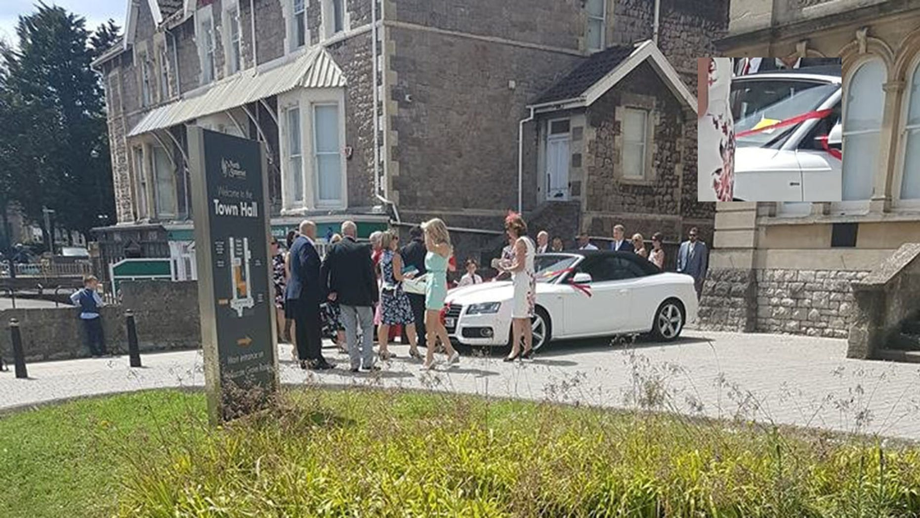 These images appear to show a happy couple being given a parking ticket on their wedding day - but it was placed on the windscreen as a prank. See SWNS story SWWEDDING; The white Audi convertible parked outside the registry office in Weston-Super-Mare, North Somerset, has what looked like a bright yellow parking ticket on the windscreen. Guests could be seen mingling around outside the town hall dressed in smart clothes. Freya Shepherd, who was passing by, spotted the suspected Penalty Charge Notice (PCN) and was shocked that a traffic warden could be so mean-spirited.