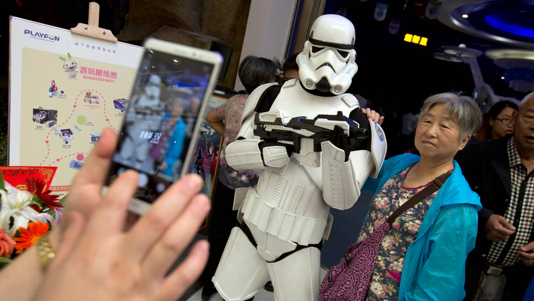 A Chinese woman poses for a photo with a worker dressed in a storm trooper costume at the Wanda Mall outside of the Wanda Cultural Tourism City in Nanchang in southeastern China's Jiangxi province, Saturday, May 28, 2016. The Walt Disney Co. owns the rights to Lucas Film and associated properties.