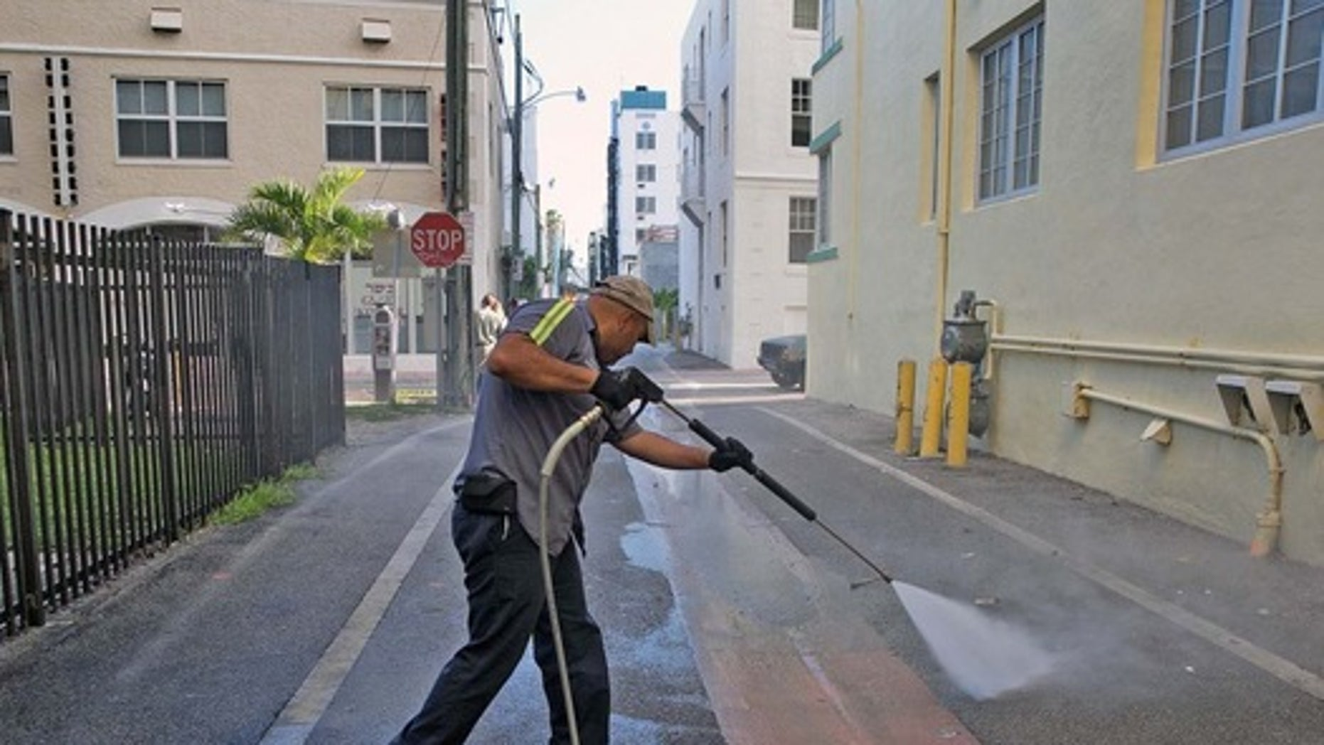 A worker from the Miami Beach Sanitation Dept., washes down alley ways Friday, Aug. 19, 2016, Miami Beach, Fla., with a high pressure water machine set to 250 degrees Fahrenheit, which kills any bacteria or mosquito larvae that could be growing in still waters.