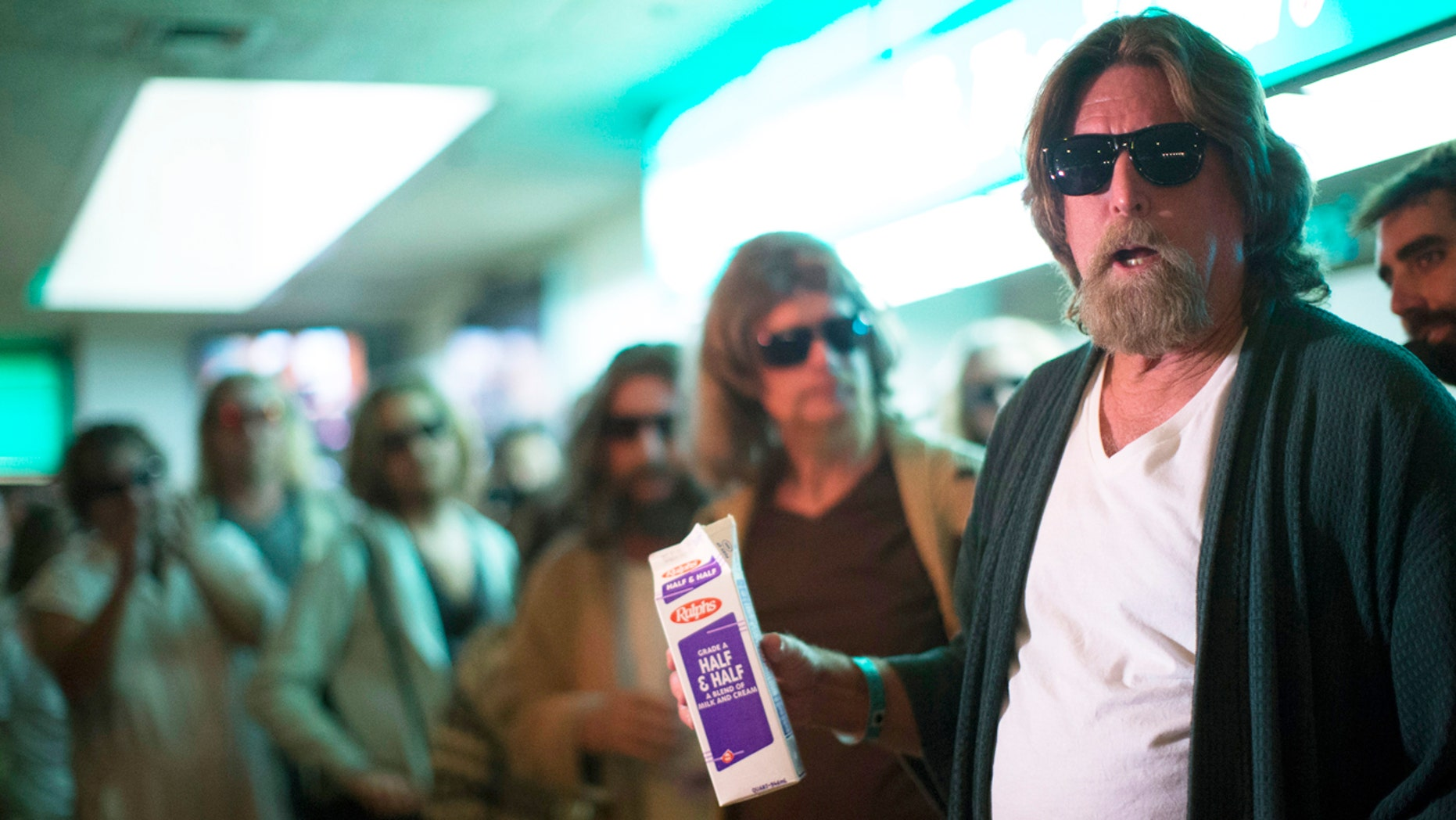 """Mike Ritto (R) and other enthusiasts wear costumes resembling characters from the movie """"The Big Lebowski"""" at the Lebowski Fest LA Bowling Party in Fountain Valley, California."""