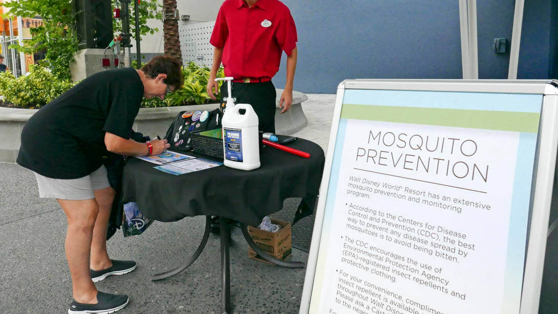 A tourist stops by a station giving out free mosquito repellant at Disney Springs in Lake Buena Vista, Fla. on Tuesday Sept. 13, 2016.