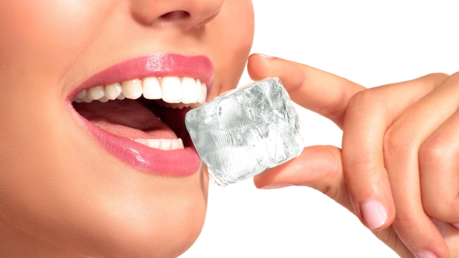 Closeup of beautiful woman biting an ice cube on white