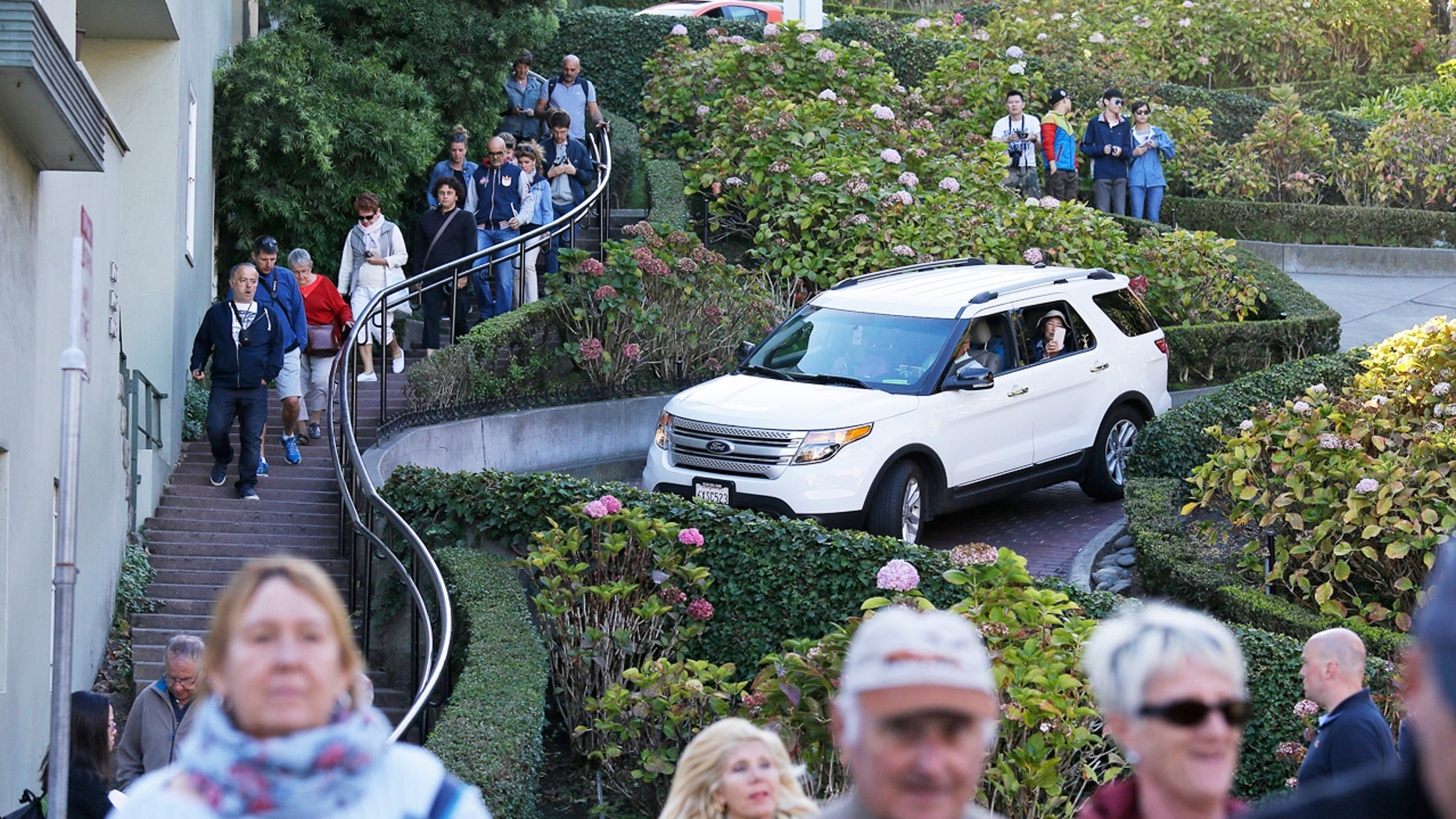 """Tourists make their way down Lombard Street, also known as the """"most crooked street"""" in San Francisco. The crooked block has become so chaotic that the city of San Francisco is considering solutions as drastic as banning cars or requiring timed reservations."""