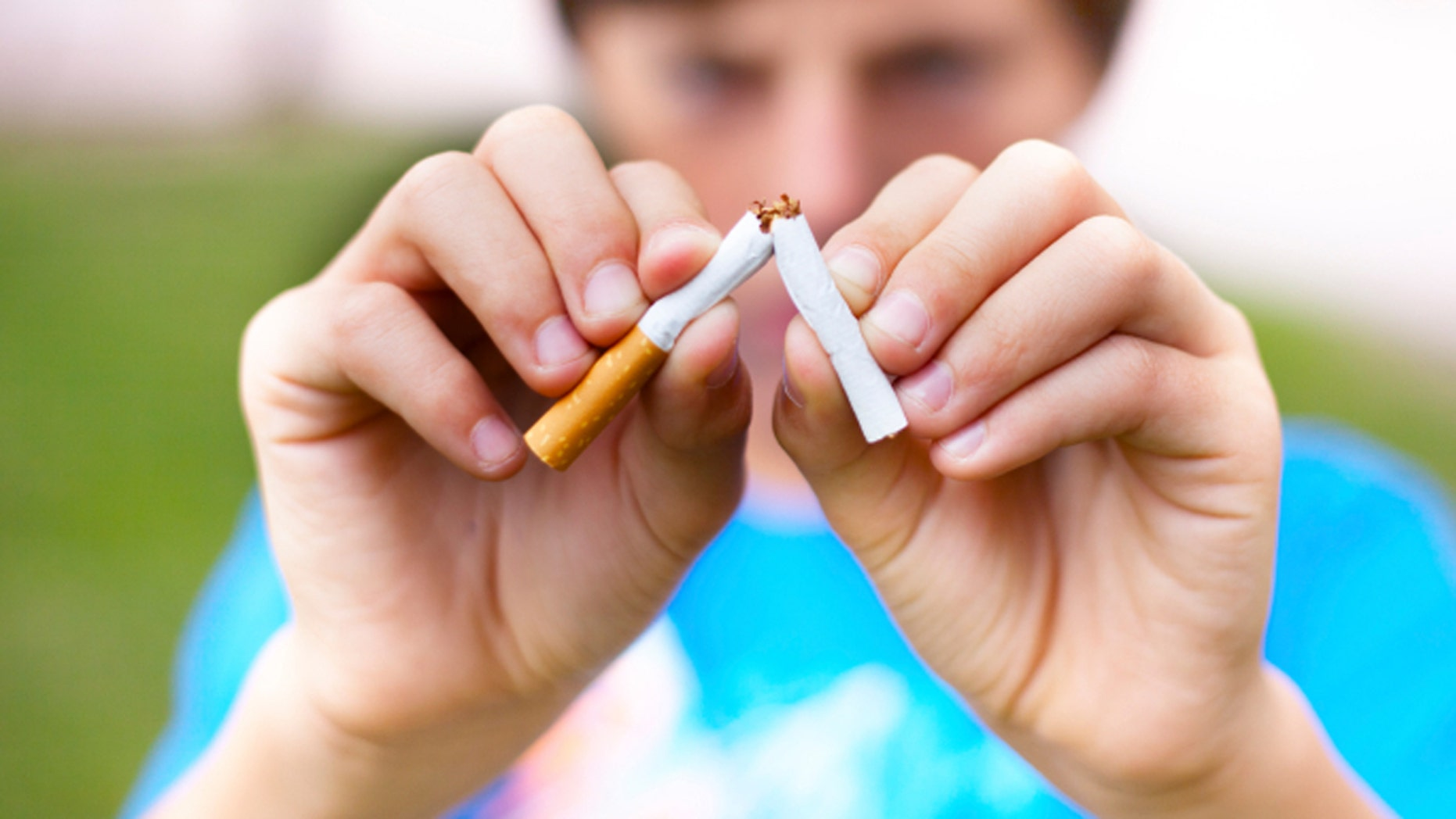 Young boy breaks a cigarette. Selective focus.