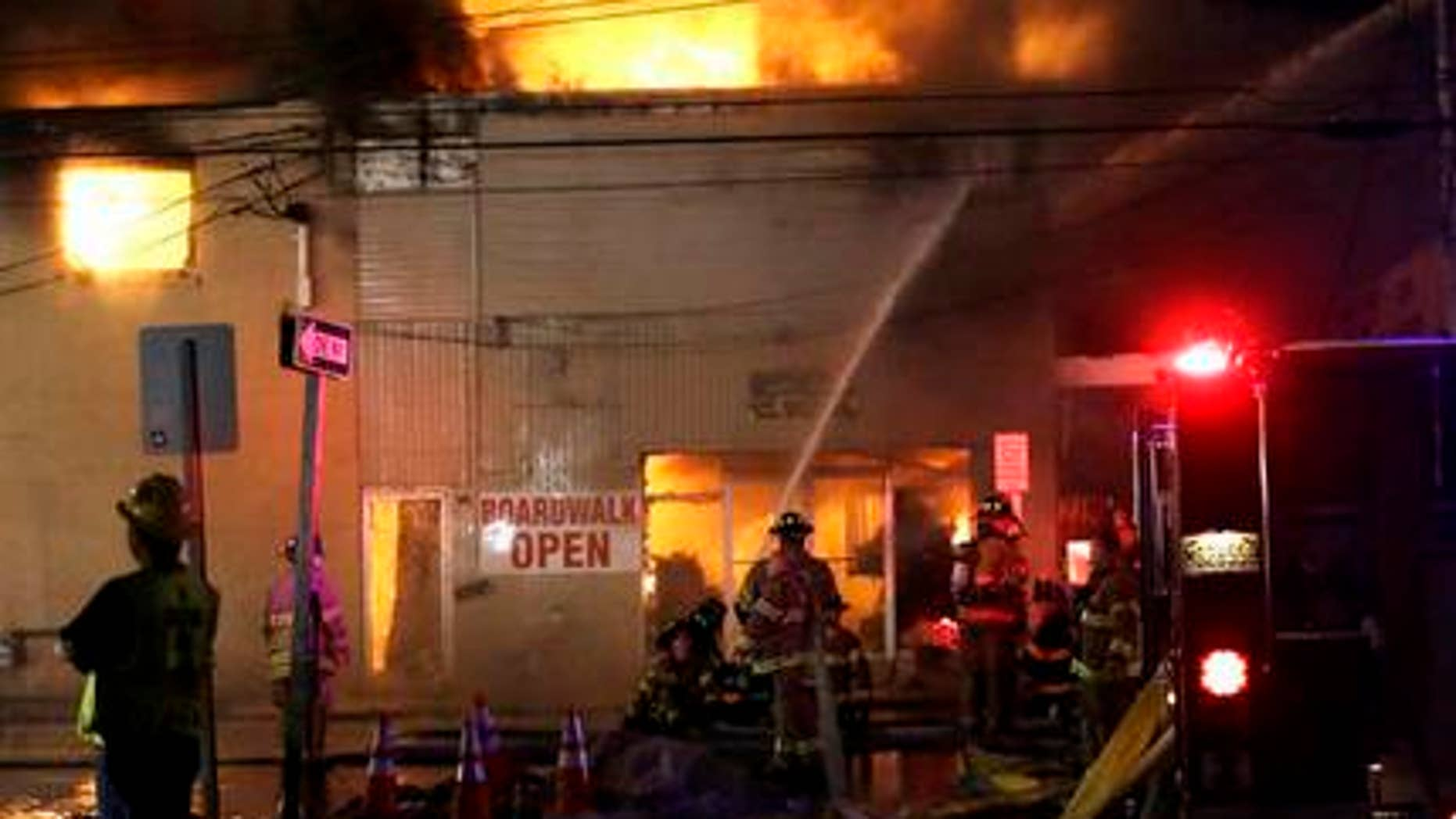 In this Thursday, Sept. 12, 2013, file photograph, firefighters battle a blaze in a building along the Seaside Park boardwalk in Seaside Park, N.J. The historic Jersey shore pier that was pummelled by Superstorm Sandy, then destroyed in a spectacular fire may finally be done in by building regulations. The owner of the former Funtown Pier in Seaside Park, said he won't rebuild it if the town sticks to height restrictions it wants to impose on rides on a rebuilt pier.