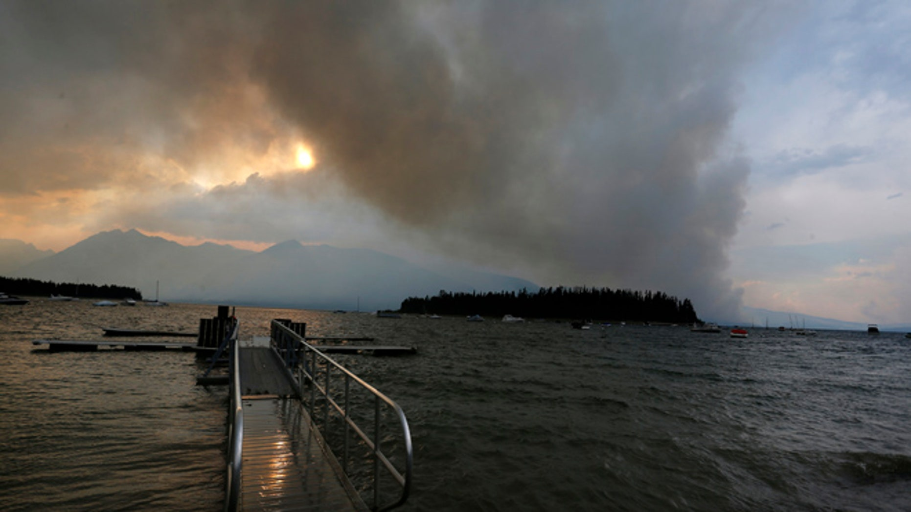 A wildfire is visible from Leek's Marina on the shore of Jackson Lake, in Grand Teton National Park, Wyo., Wednesday, Aug. 24, 2016.