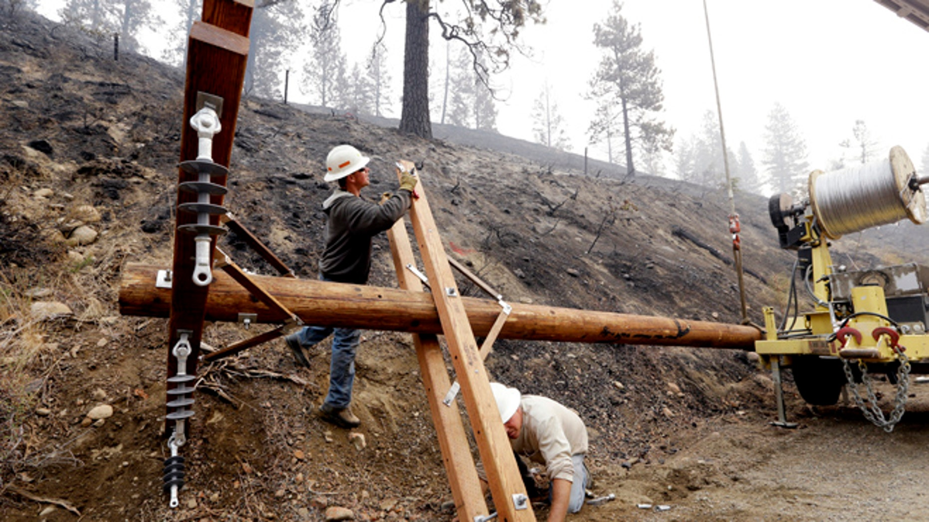 Aug. 23, 2015: Utility workers Chris Zahn, left, and Dan Foussard work to assemble a new pole to replace one of about 50 that burned down along Twisp River Road in a wildfire days earlier in Twisp, Wash.