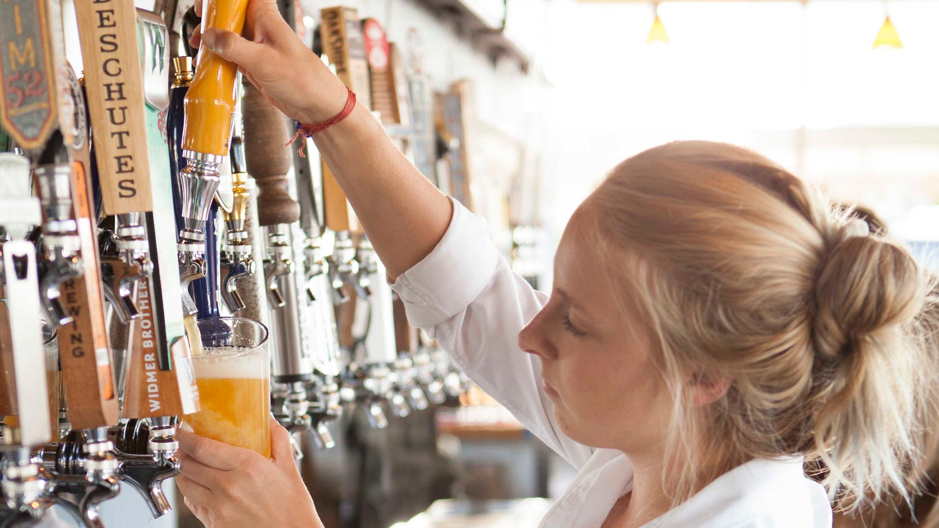 A server taps a pint of craft beer.