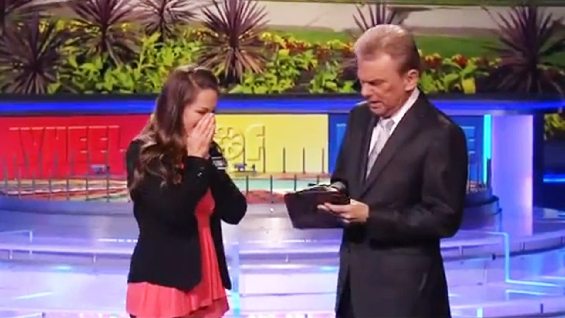 "Autumn Ernhard stands beside Pat Sajack after winning $1 million on ""Wheel of Fortune."""