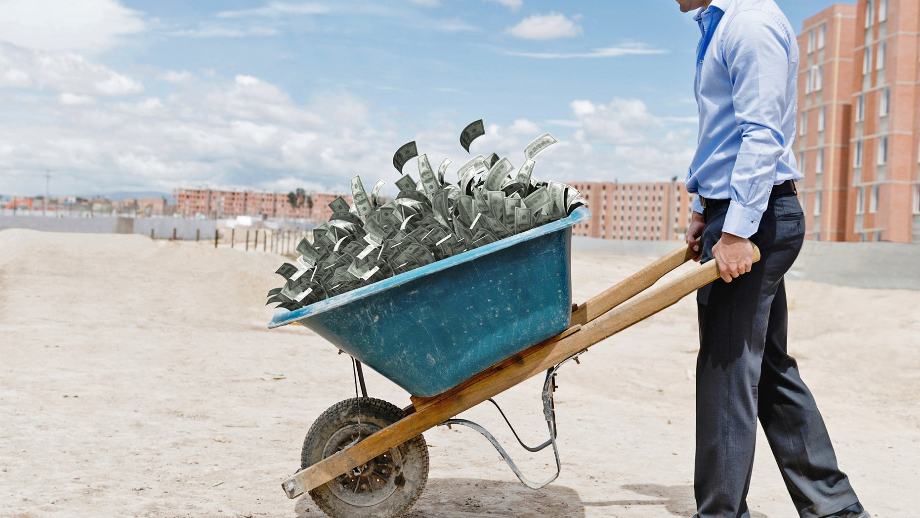 Man with wheelbarrow full of money