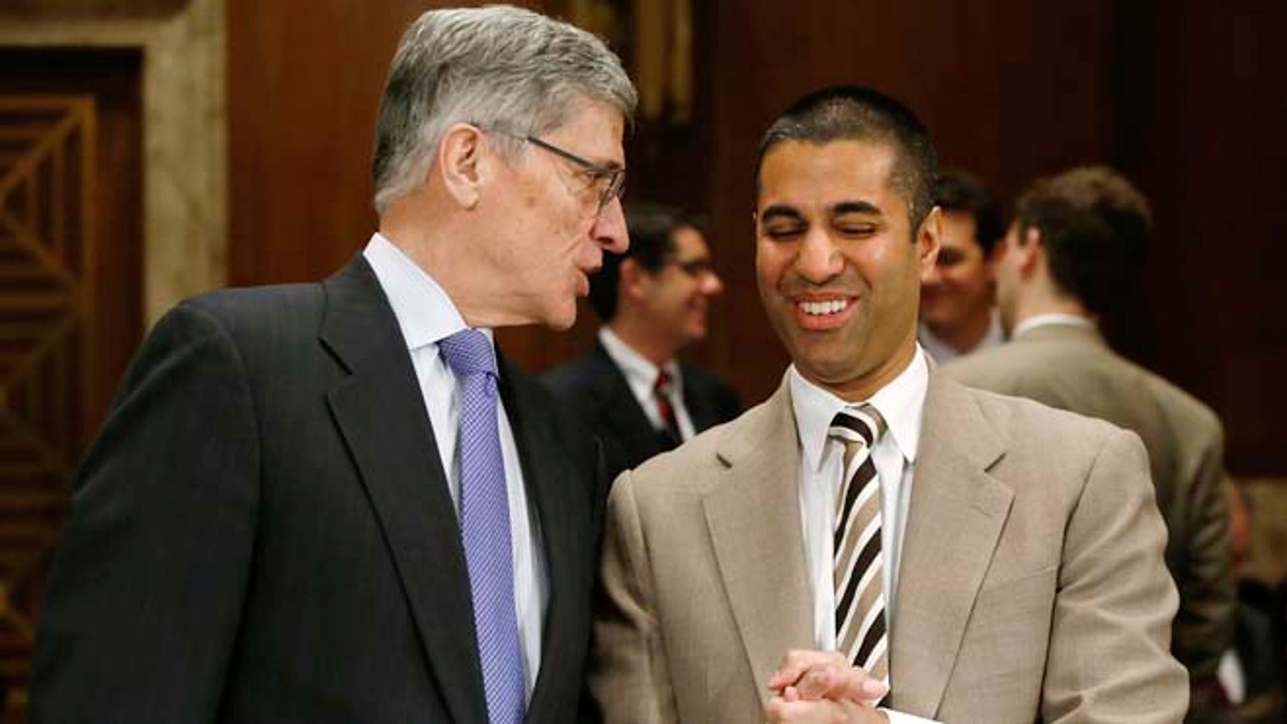 In this March 27, 2014 photo, Federal Communications Commission (FCC) Chairman Tom Wheeler, left, and FCC Commissioner Ajit Pai arrive to testify before a Senate subcommittee in Washington, D.C.