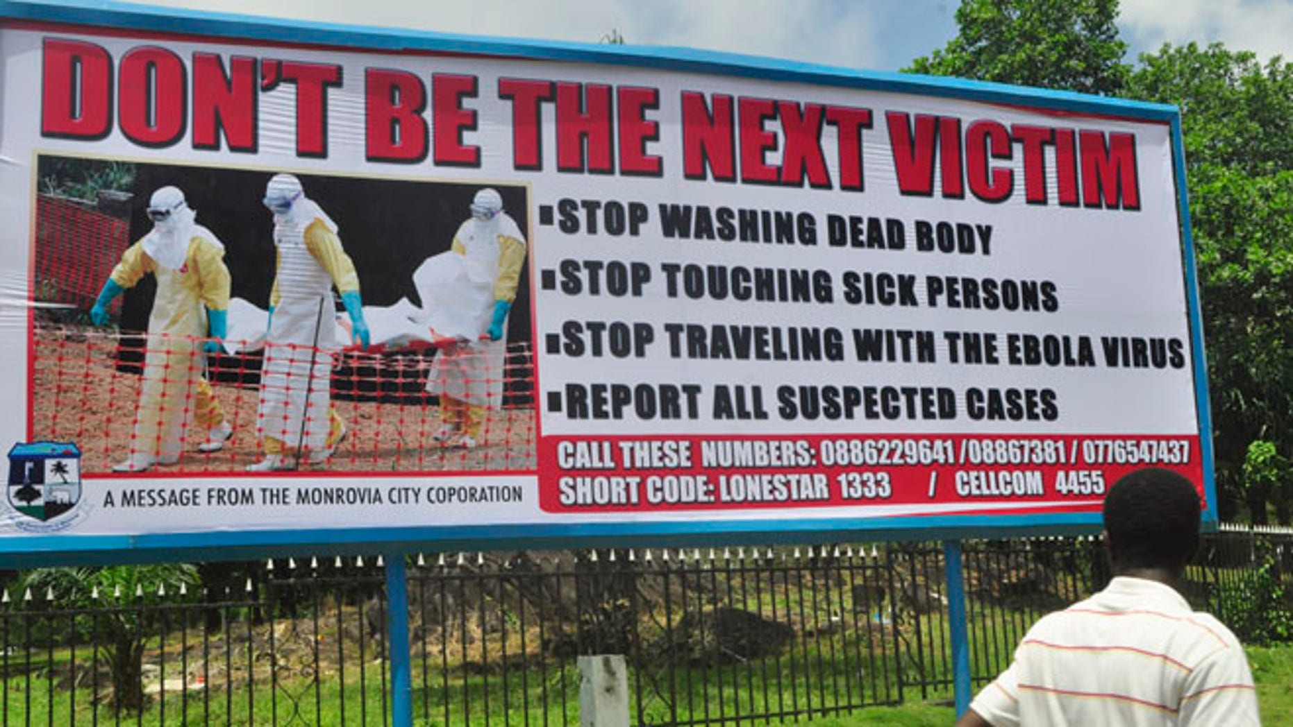 Oct. 10, 2014: A man walks past a billboard warning people of the deadly Ebola virus in Monrovia, Liberia