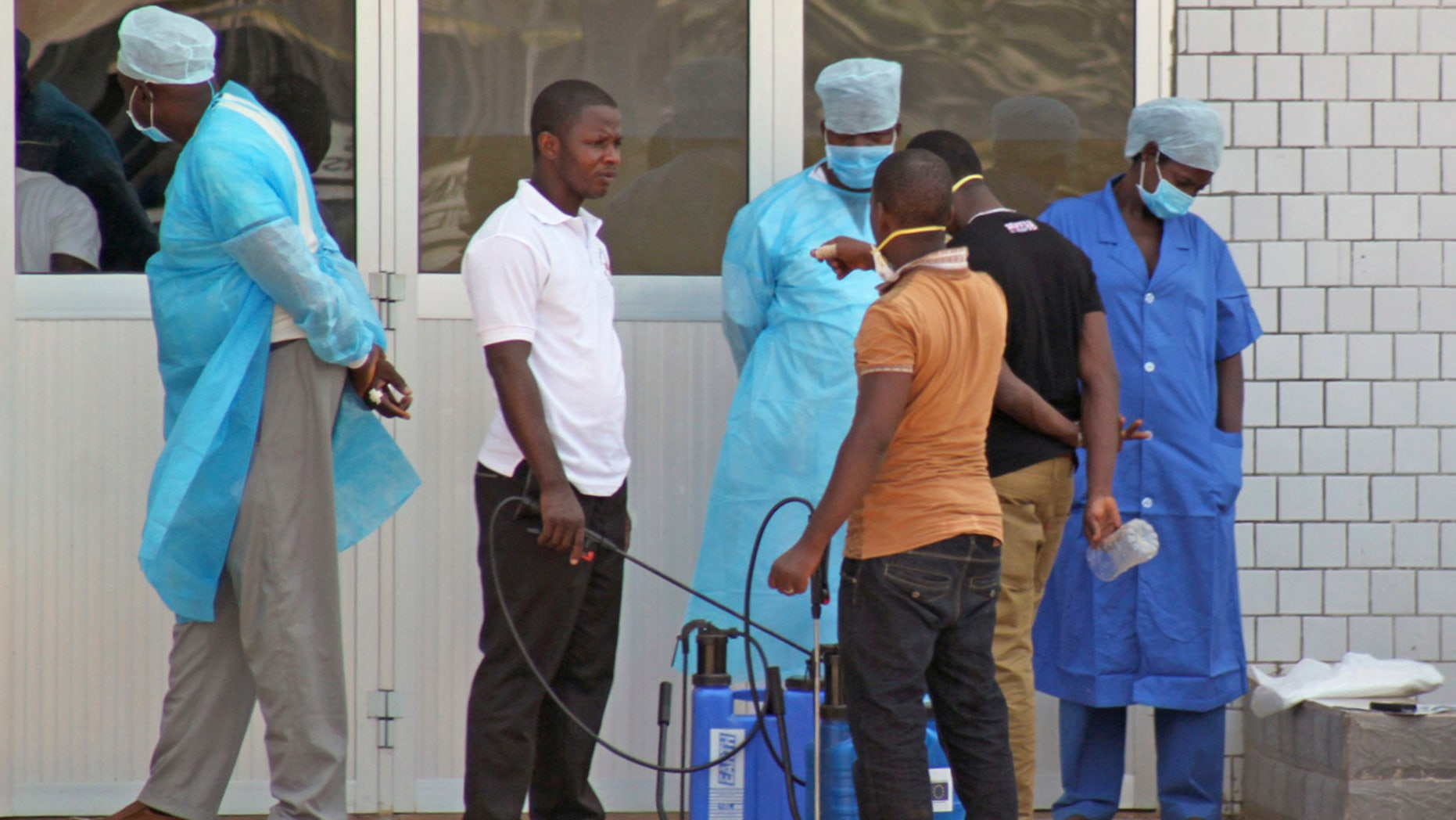 FILE - In this March 29, 2014, file photo, medical personnel at the emergency entrance of a hospital wait to receive suspected Ebola virus patients in Conakry, Guinea.