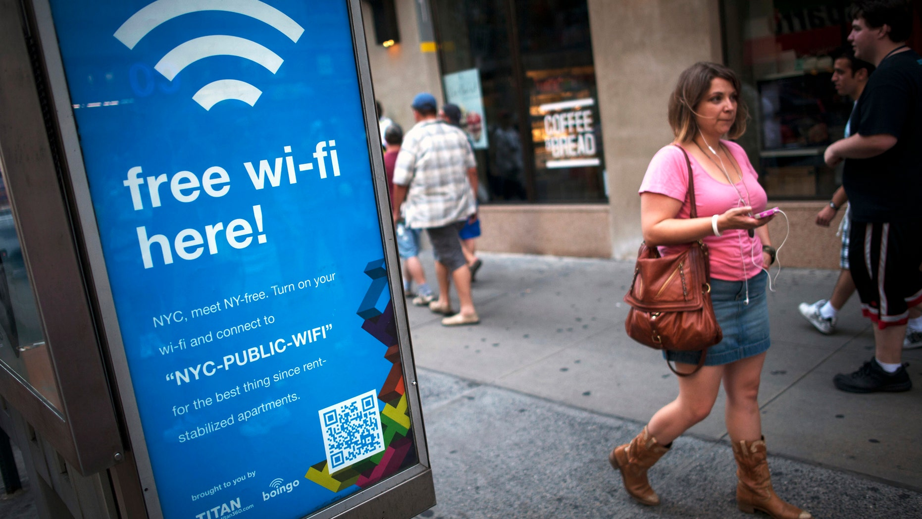 File photo: A woman walks past a WiFi-enabled phone booth in New York July 12, 2012. (REUTERS/Keith Bedford)