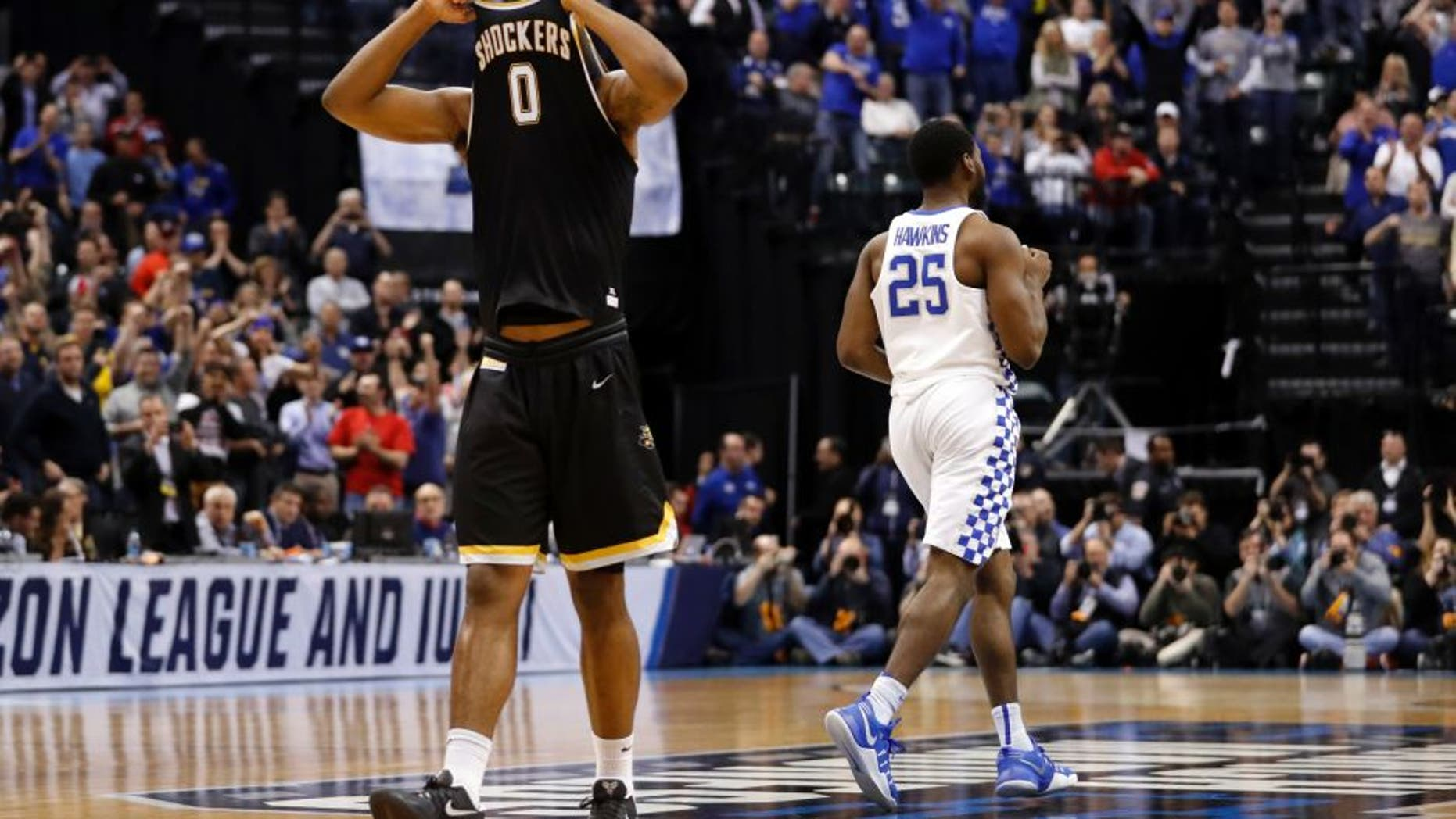 Wichita State's Rashard Kelly (0) hides his face as Kentucky's Dominique Hawkins (25) heads to celebrates with his teammates following a second-round game in the men's NCAA college basketball tournament Sunday, March 19, 2017, in Indianapolis. Kentucky won 65-62. (AP Photo/Jeff Roberson)