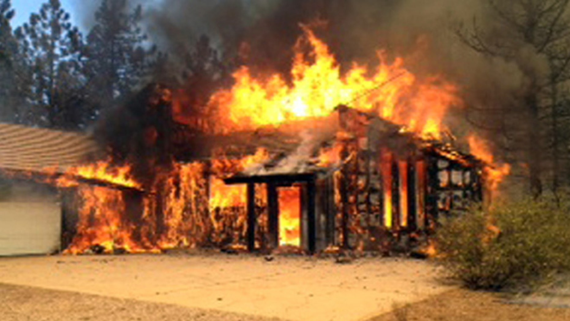 July 3, 2014: In this still frame from video provided by KNSD-TV, a home is fully involved in flames as crews scrambled to corral a wildfire that burned two homes near the San Diego County mountain town of Julian in Southern California.
