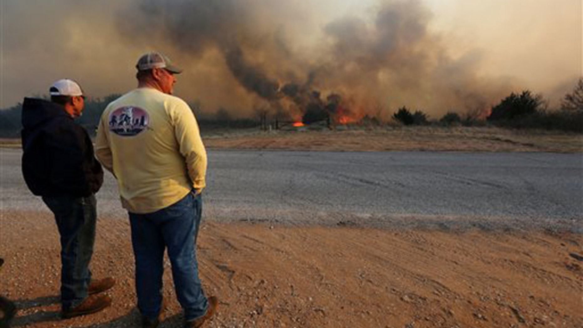 Jeff Clark and Roger Van Rankin watch the fire east of Lake City, Kan., Wednesday, March 23, 2016. The two were watching to see if the fire would jump the road onto Clark's ground.
