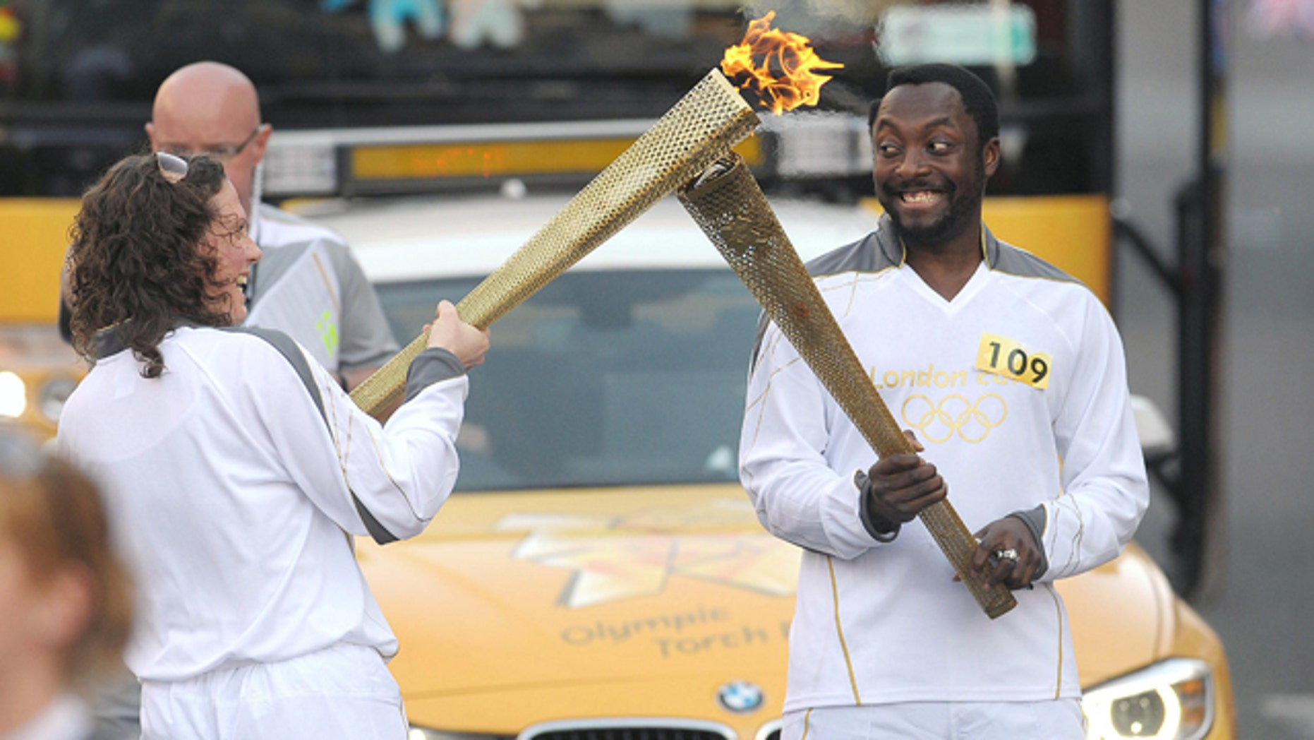 May 21, 2012: Will.i.am of the Black Eyed Peas passes the Olympic Flame to torchbearer Emma Fowler in Taunton, southwest England.