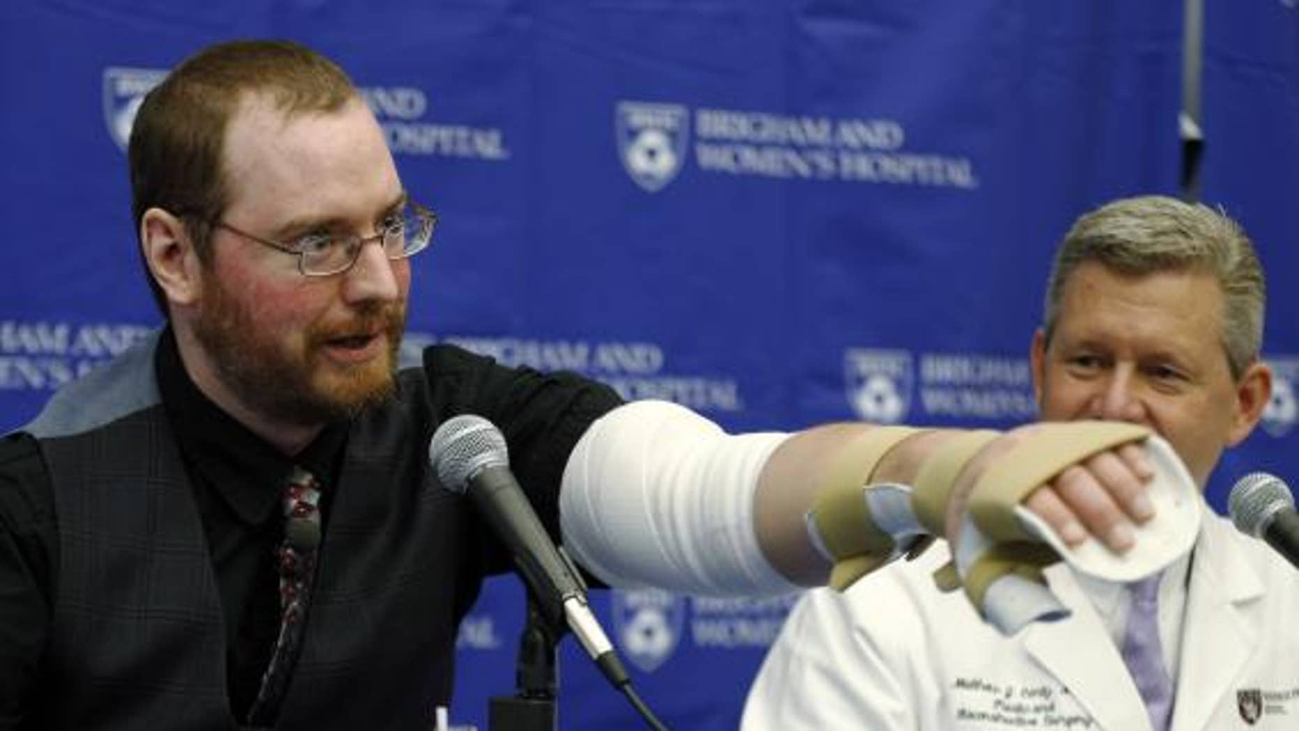 Nov. 25, 2014: Will Lautzenheiser (L) demonstrates some of the motion in his left arm as Dr. Matthew Carty, a member of his transplant team, looks on at a news conference to announce Lautzenheiser's successful double arm transplant at Brigham and Women's Hospital in Boston, Massachusetts.