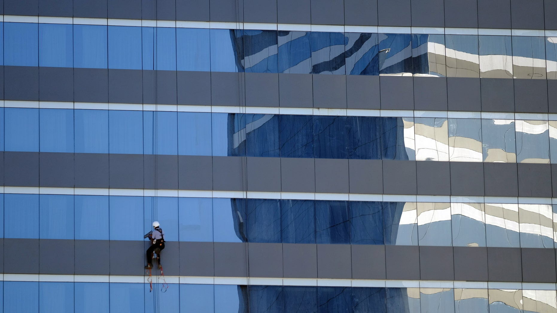 A window washer works outside a Marriott hotel near the Olympic Park before the start of the Rio 2016 Olympics in Rio de Janeiro, August 1, 2016. Picture taken August 1, 2016.