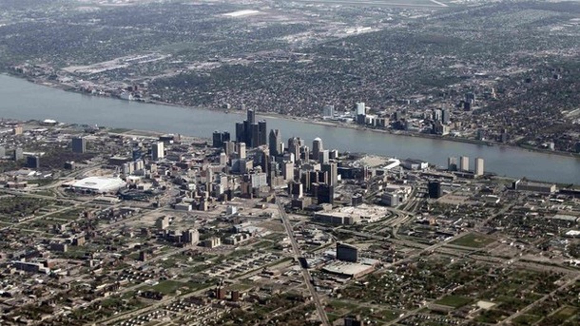 An aerial view of Detroit, Mich., seen in the foreground, while Windsor, Ontario lies on the opposite side of the Detroit River.