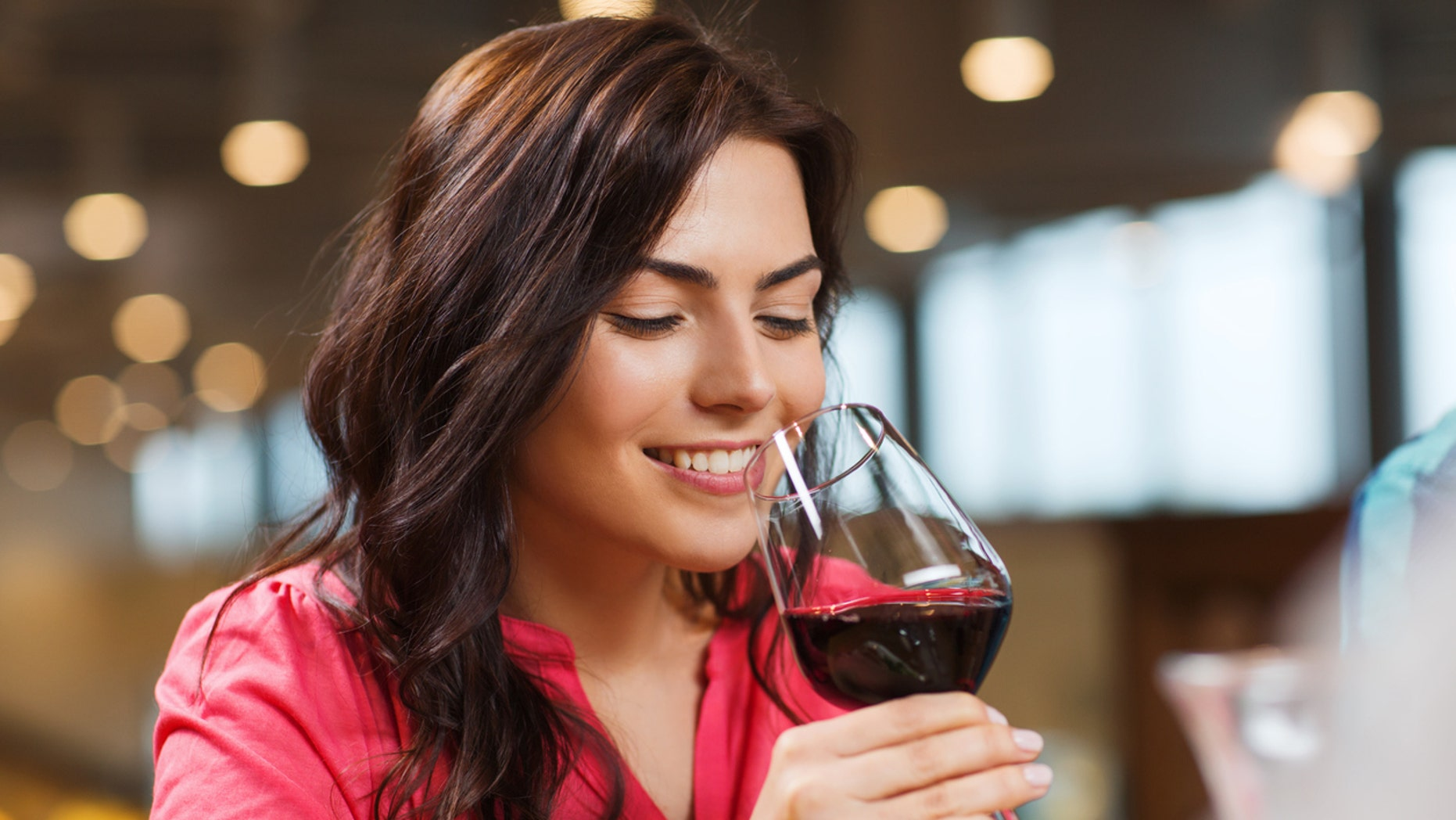 leisure, drinks, degustation, people and holidays concept - smiling woman drinking red wine at restaurant