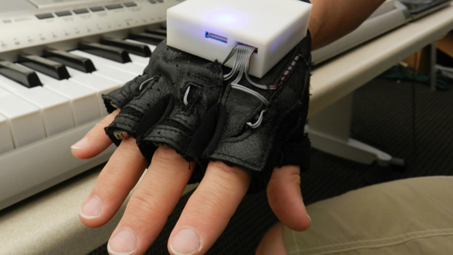 The glove, which looks like a workout glove with a small box on the back, is used with a piano keyboard and vibrates a persons fingers to indicate which keys to play. While learning to play the instrument, several people with SCI experienced improved sensation in their fingers.