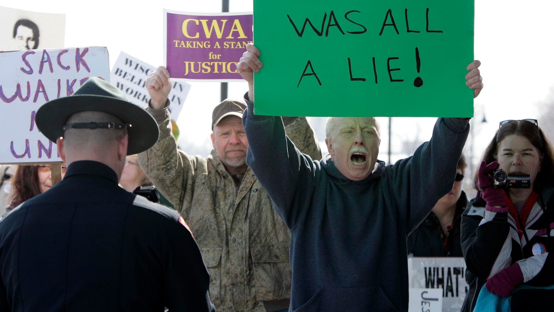 Dan Schierl of Neenah, Wis., second from right, joins other protesters during Gov. Scott Walker's announcement from the Fox Cities Trestle Trail over Little Lake Butte Des Morts Thursday, March 31, 2011 in Menasha, Wis. (AP)
