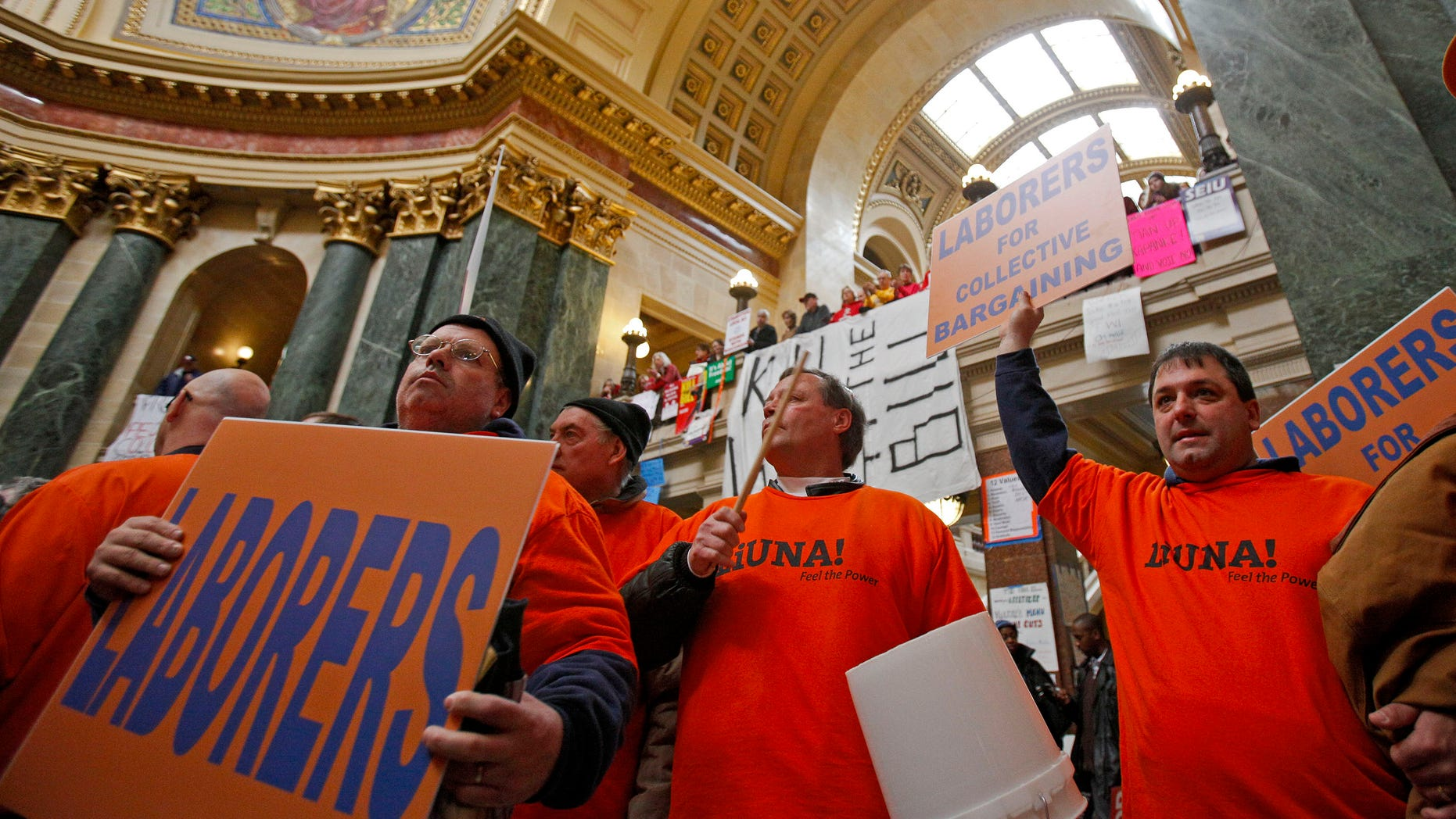 Union worker Dan Burke, center, of Janesville, Wis., uses a bucket to drum after loosing his voice during protests at the state Capitol in Madison, Wis., Friday, Feb. 25, 2011, over the governor's proposed budget. (AP)