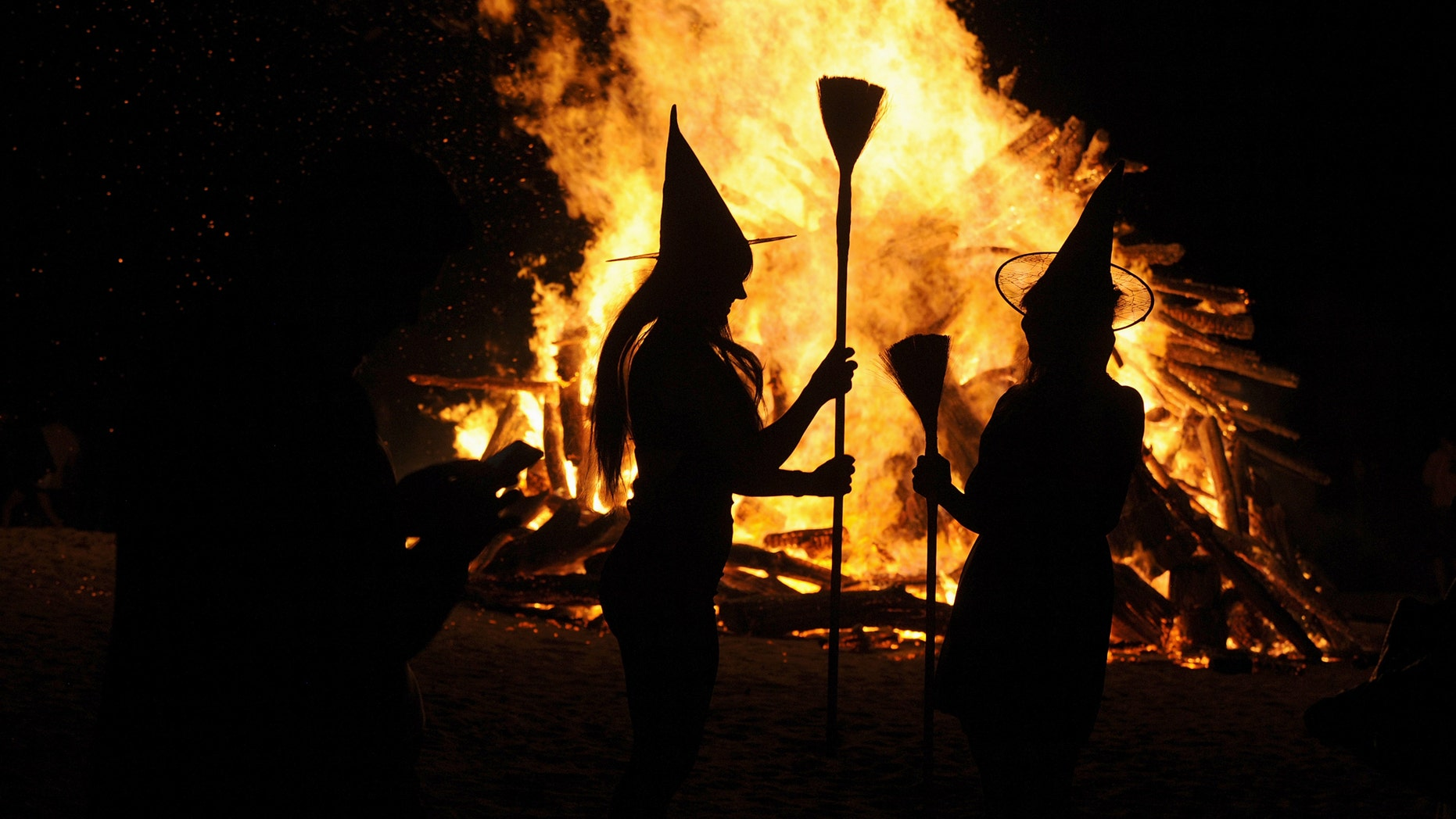File photo: Two women dressed up as witches take pictures in front of the bonfire during the traditional San Juan's (Saint John) night on the beach in Gijon, northern Spain, June 24, 2015. (REUTERS/Eloy Alonso TPX)