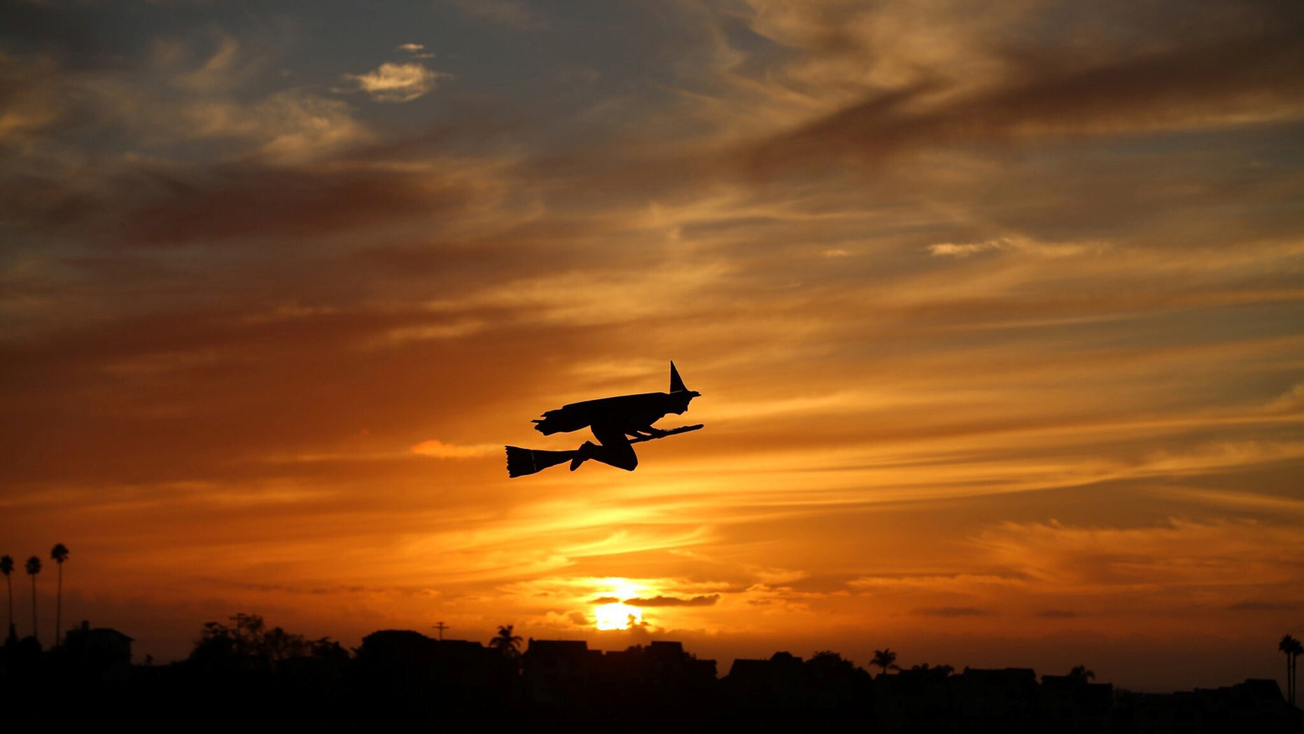 File photo - A remote-controlled plane in the form of a witch flies over a neighborhood as the sun sets during Halloween in Encinitas, California, U.S. Oct. 31,2016. (REUTERS/Mike Blake)