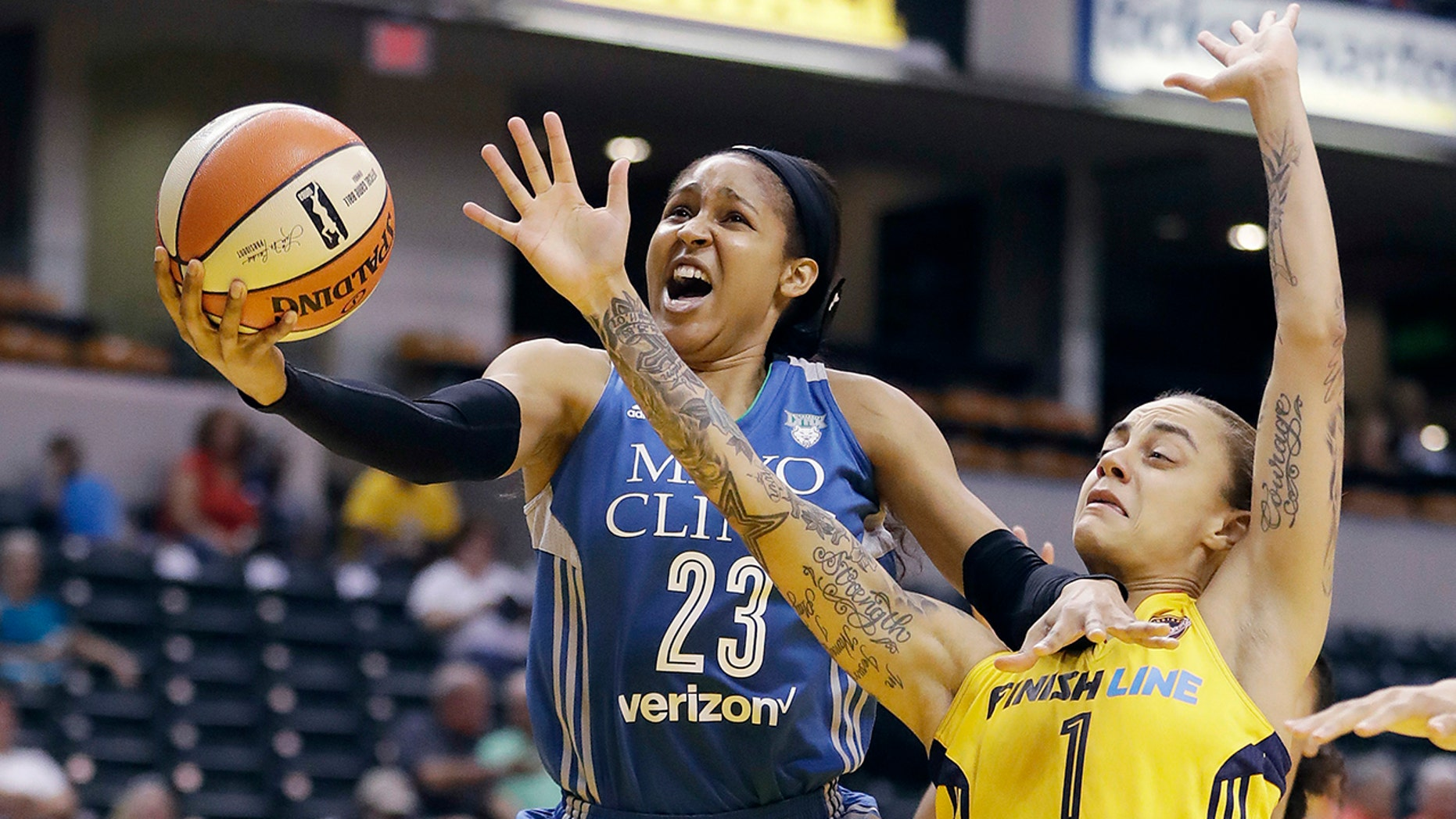 Minnesota Lynx's Maya Moore, left, shoots against Indiana Fever's Jazmon Gwathmey during the first half of a WNBA basketball game in Indianapolis.