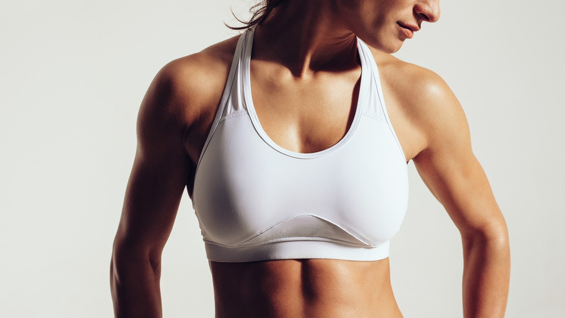 Portrait of fit woman in sports bra with muscular body against grey background. Close-up studio shot of female fitness model in sports wear.