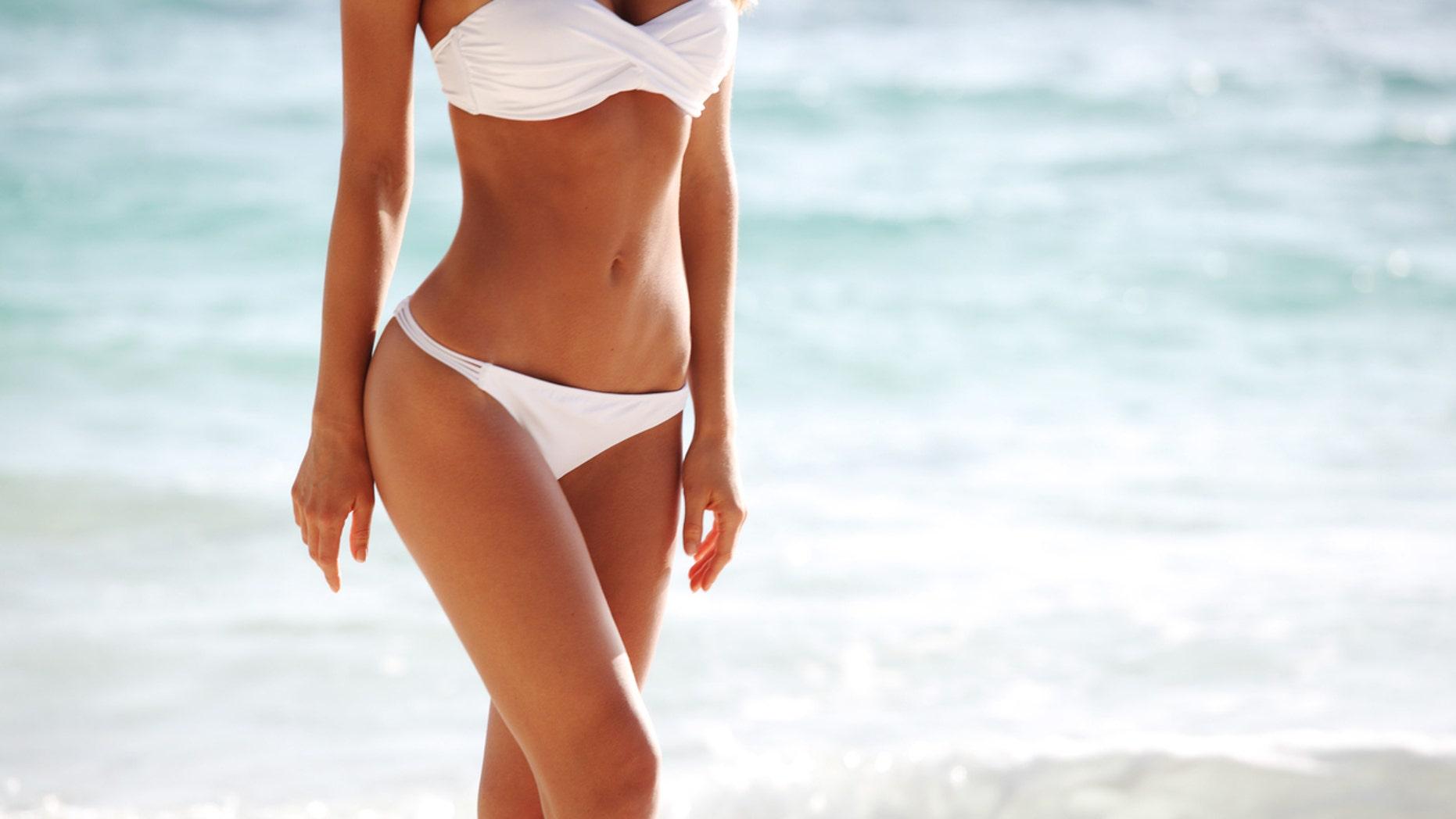 Sexy woman body in bikini on the beach background