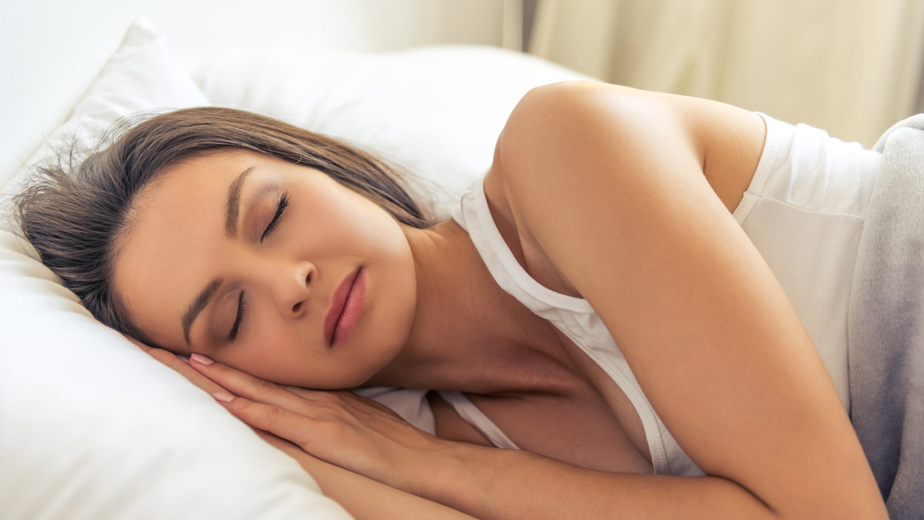 Side view of beautiful young woman sleeping in her bed at home