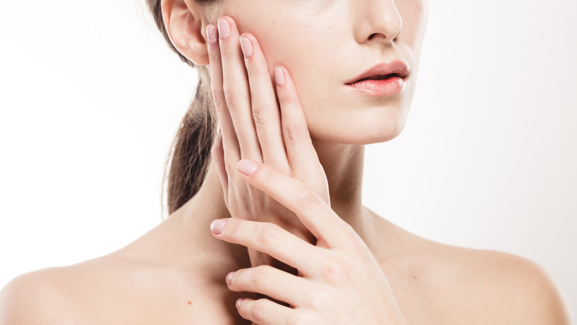 Woman shoulders lips hands fingers close-up portrait. Studio shot.