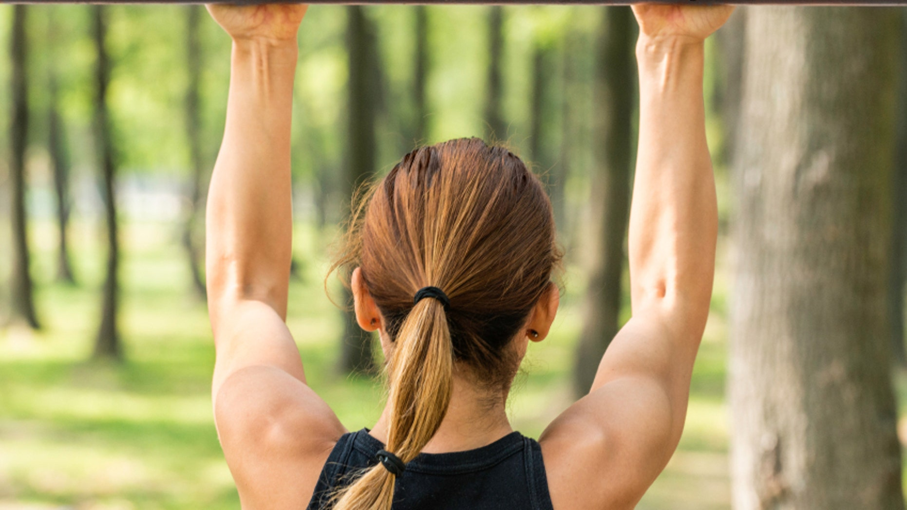 Back view of female doing pull ups outdoors