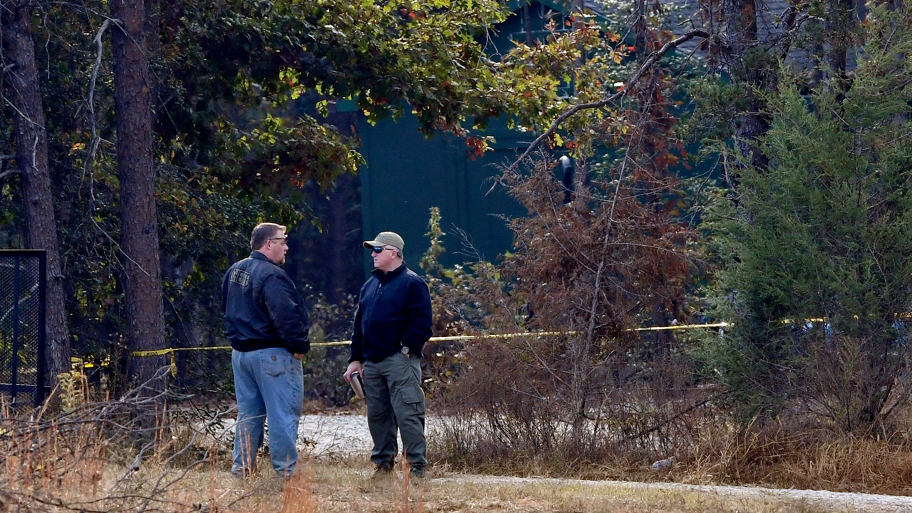 Law enforcement personnel stand near police tape on Todd Kohlhepp's property in Woodruff, S.C. Sunday, Nov. 6, 2016.