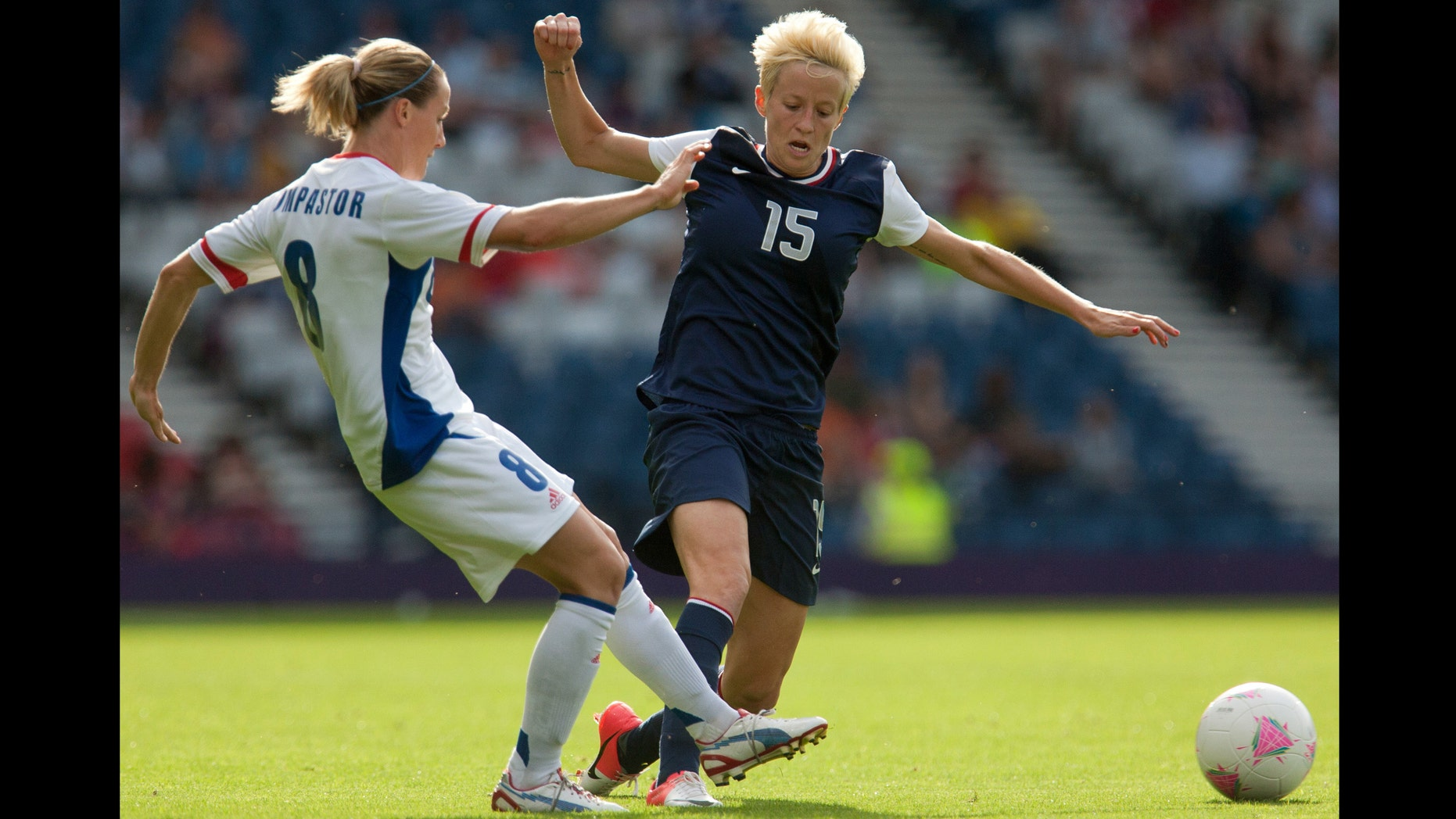France's Sonia Bompastor, left, vies for the ball with United States' Megan Rapinoe during the women's group G soccer match between the United States and France at the London 2012 Summer Olympics, Wednesday, July 25, 2012, at Hampden Park Stadium in Glasgow. (AP Photo/Chris Clark)