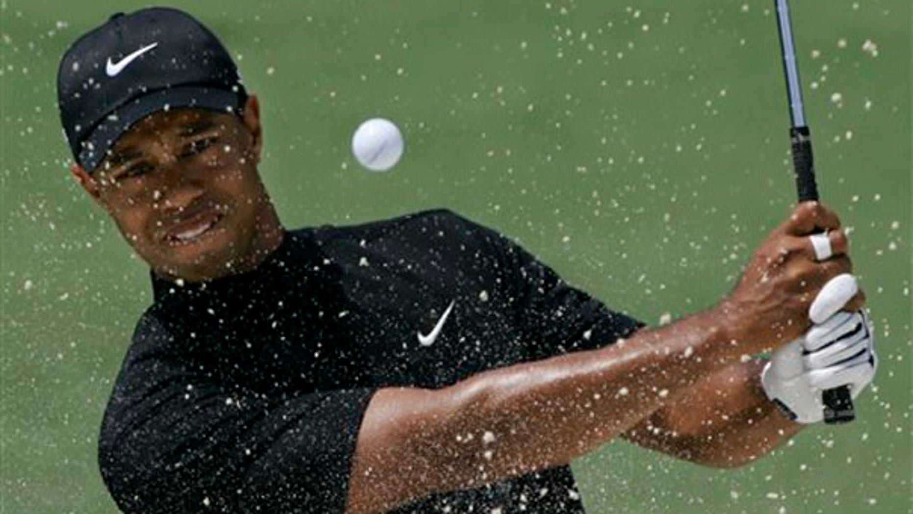 In this April 11, 2008, file photo, Tiger Woods hits out of a bunker on the second hole at the Augusta National Golf Club. (AP Photo)